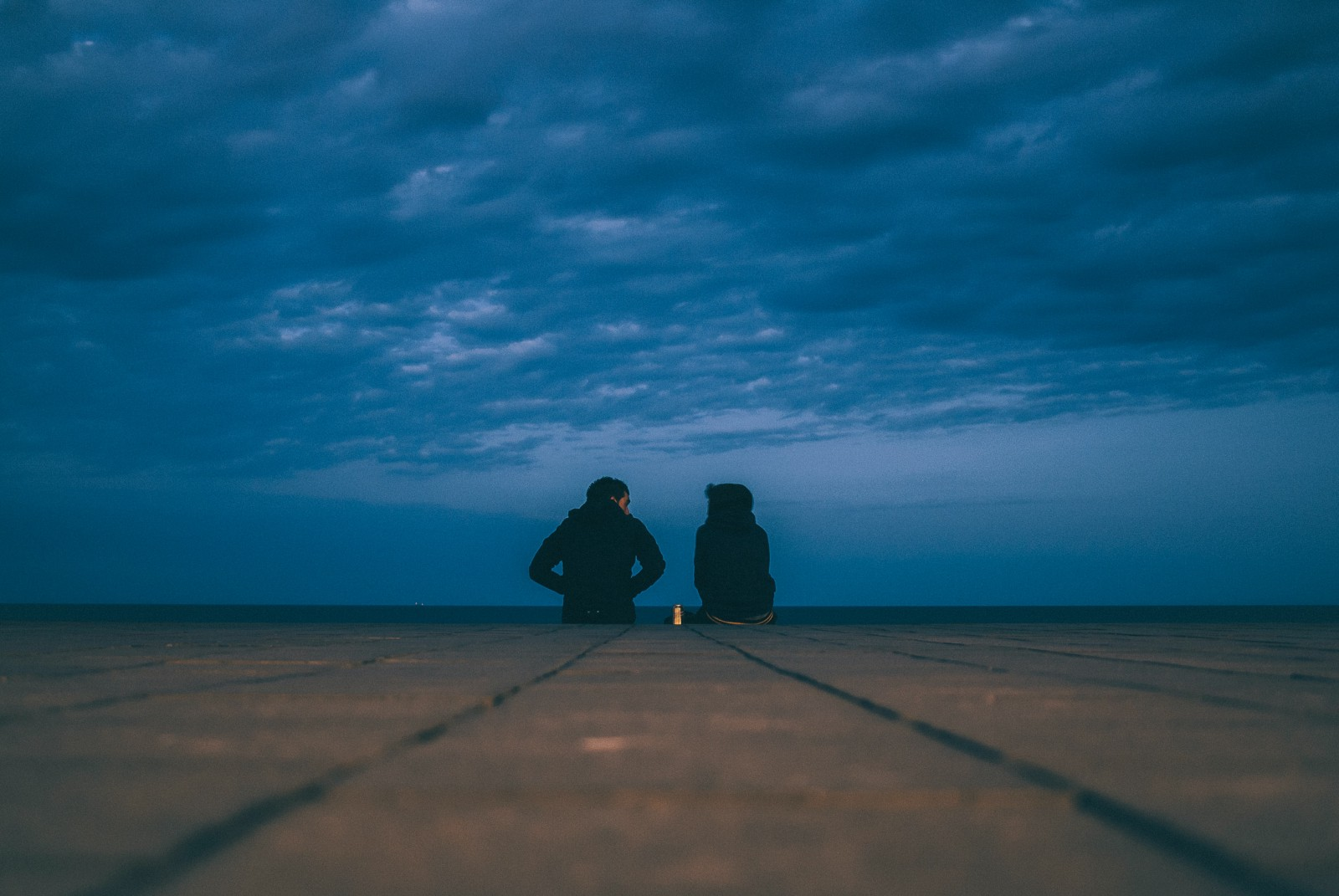 Two people sit talking at the end under a cloudy sky.