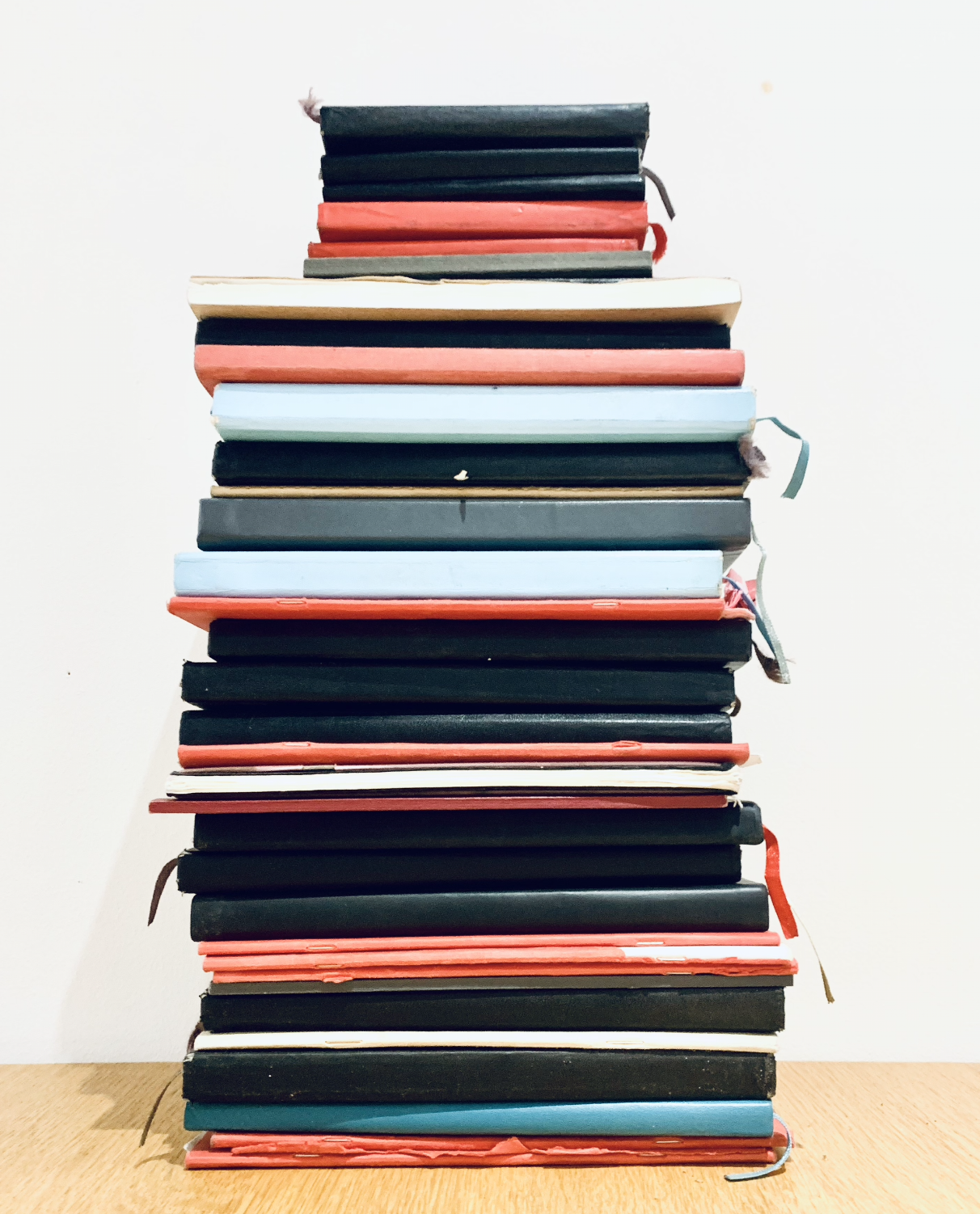 A stack of sketch books piled up in red, black and sky blue