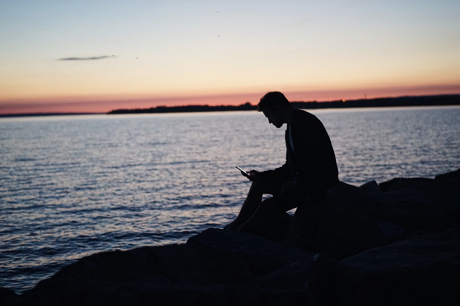 A lone figure in silhouette sits next to a large expanse of water at sunset, looking at his phone. Photo credit: Steven Spassov via Unsplash