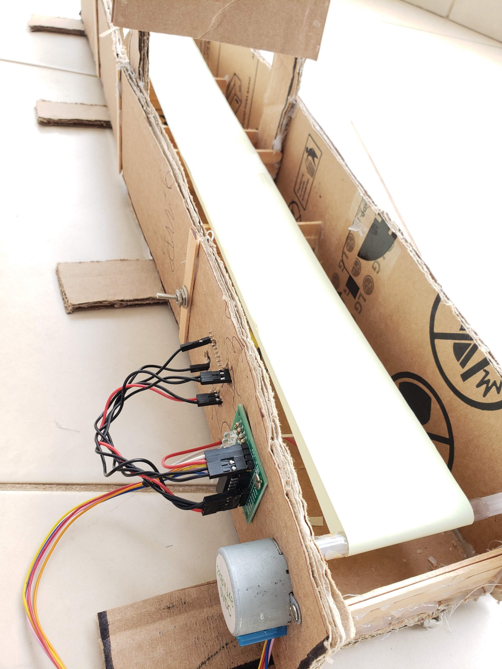 I used: Cardboard, board for ULN2003 and 28BYJ-48 5v Stepper Motor, Thermal Printer Paper Rolls, Arduino Pro Mini, and hot glue.