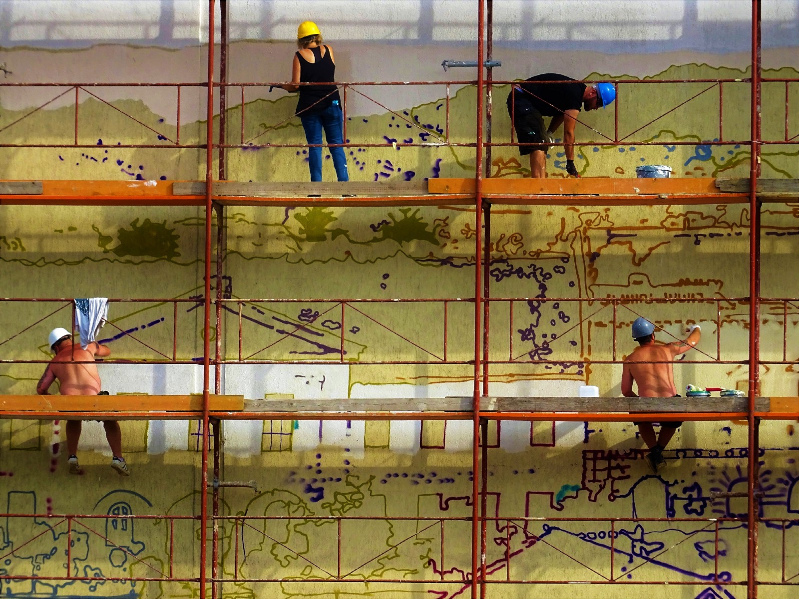 A group of people on scaffolding paint a mural.