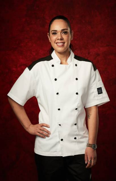 Ariel Contreras-Fox posing for Hell's Kitchen in a Chef's coat with black shoulders in front of a red background.