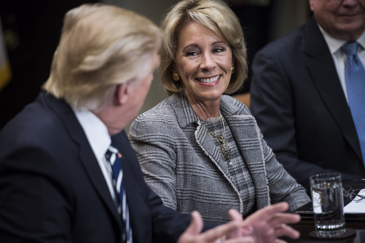 b05843bc310 President Donald Trump talks with Education Secretary Betsy DeVos by his  side during a meeting with parents and teachers in the Roosevelt Room of  the White ...