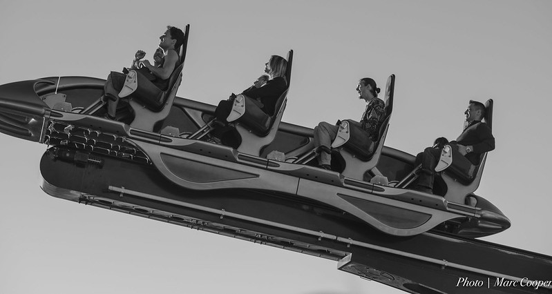 Four adults smiling as they ride a rollercoaster