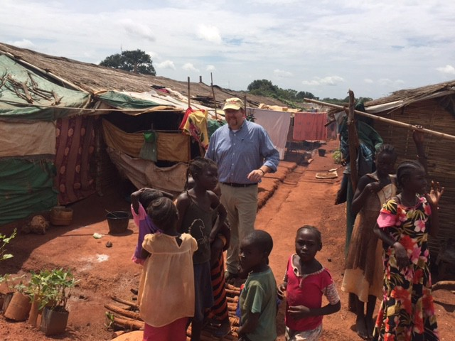 USAID officer stands behind a group of small South Sudanese children, around them are wood huts with clothes line between them.