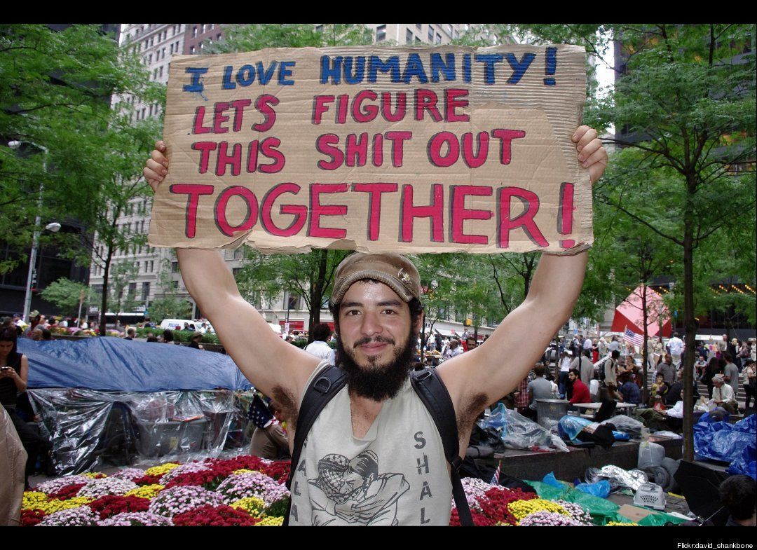 "Occupy Wall Street demonstator with sign ""I love humanity! Let's figure this shit out together!"""