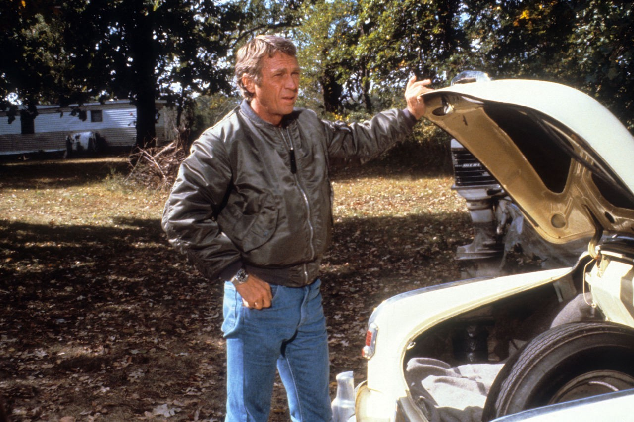 As Maverick Modern Day Bounty Hunter Ralph Papa Thorson A Military Green Blazer Jacket And Bluejeans Clad Steve Mcqueen Lifts The Trunk Of His Yellow