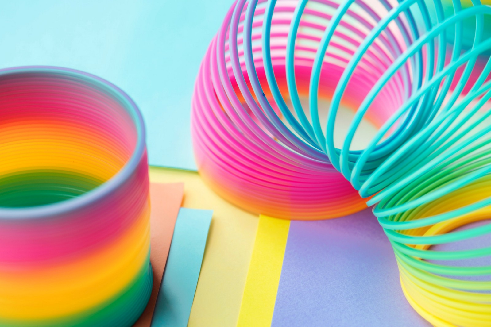 Image of rainbow multicoloured slinky toy on coloured card