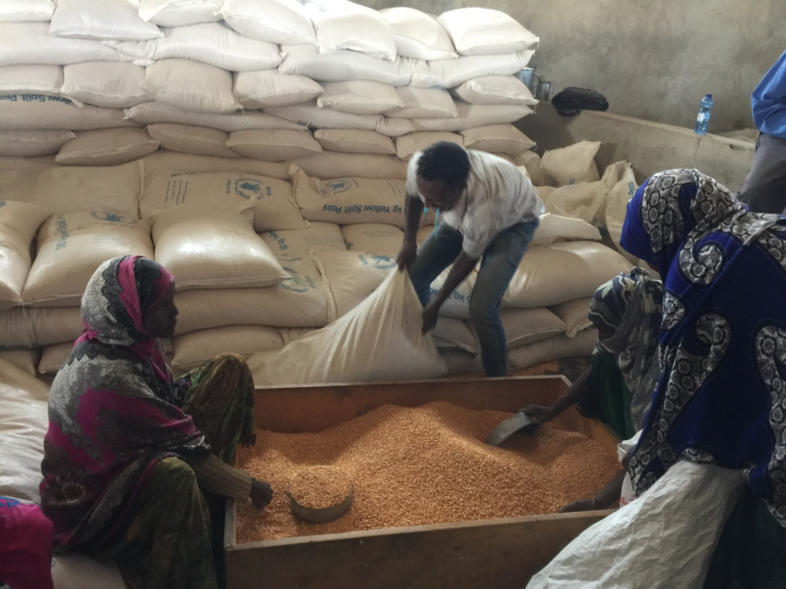 An African man and woman kneel next to a box of grain, behind them are large white bags of grain, one man is lifting a bag.
