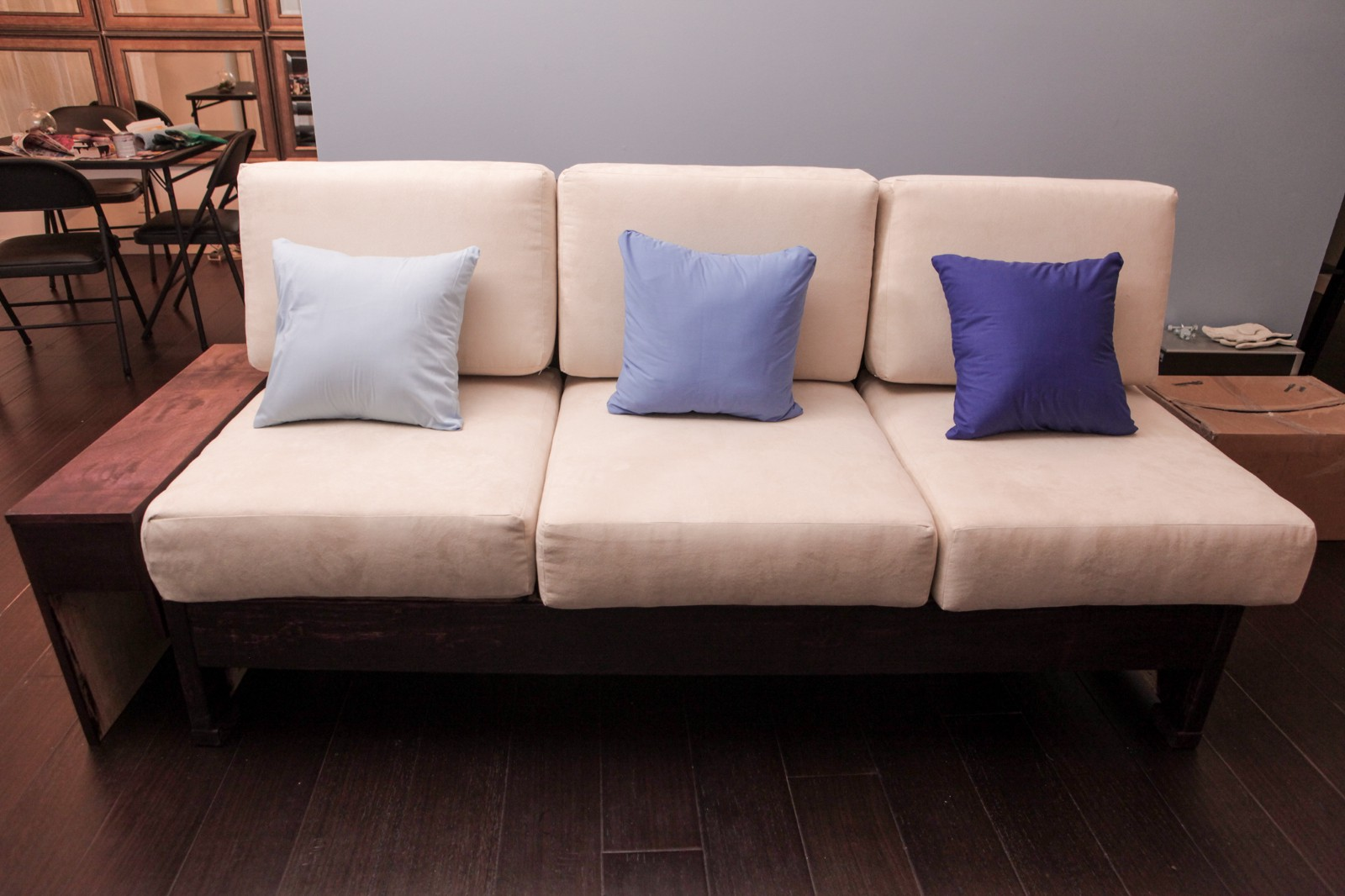 The Completed Couch With Accent Pillows And Stained Wood.