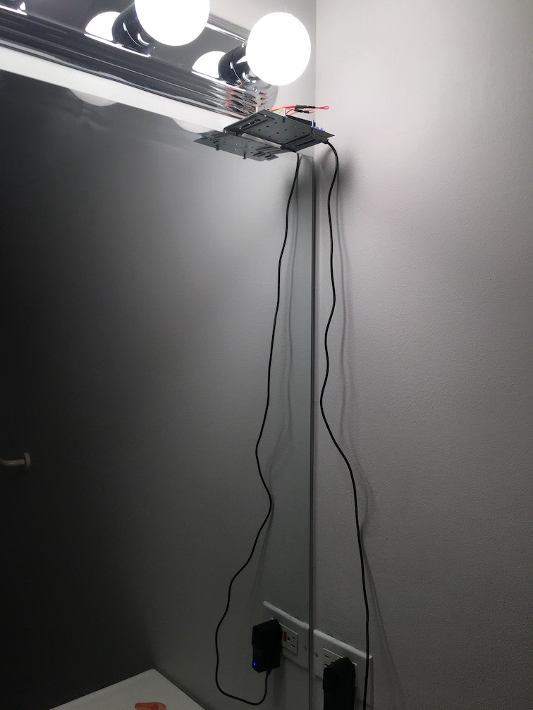 Sensor with cables hanging in the bathroom alongside the mirror.