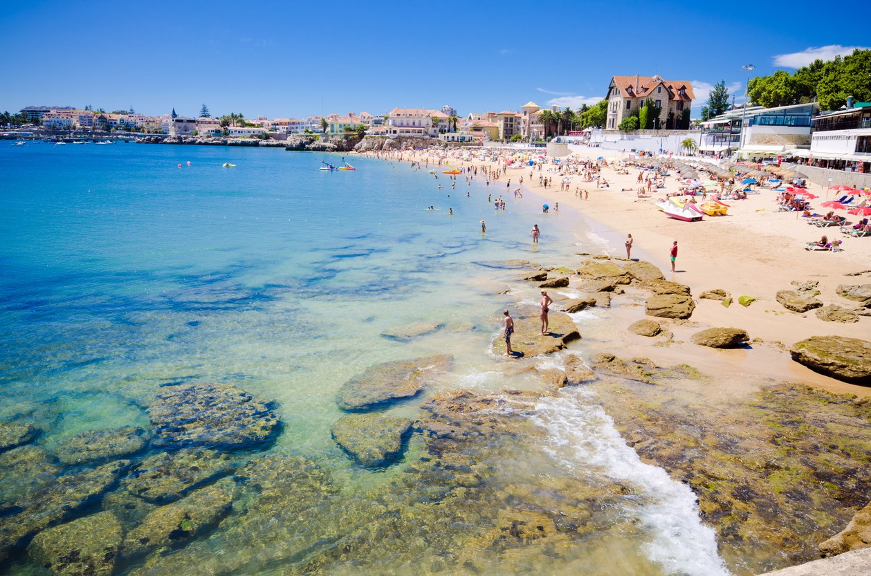 Tourists And Locals Enjoy The Clear Blue Water On A Beach In Small Town Of Cascais Hot Summer Day Istock Gregobagel