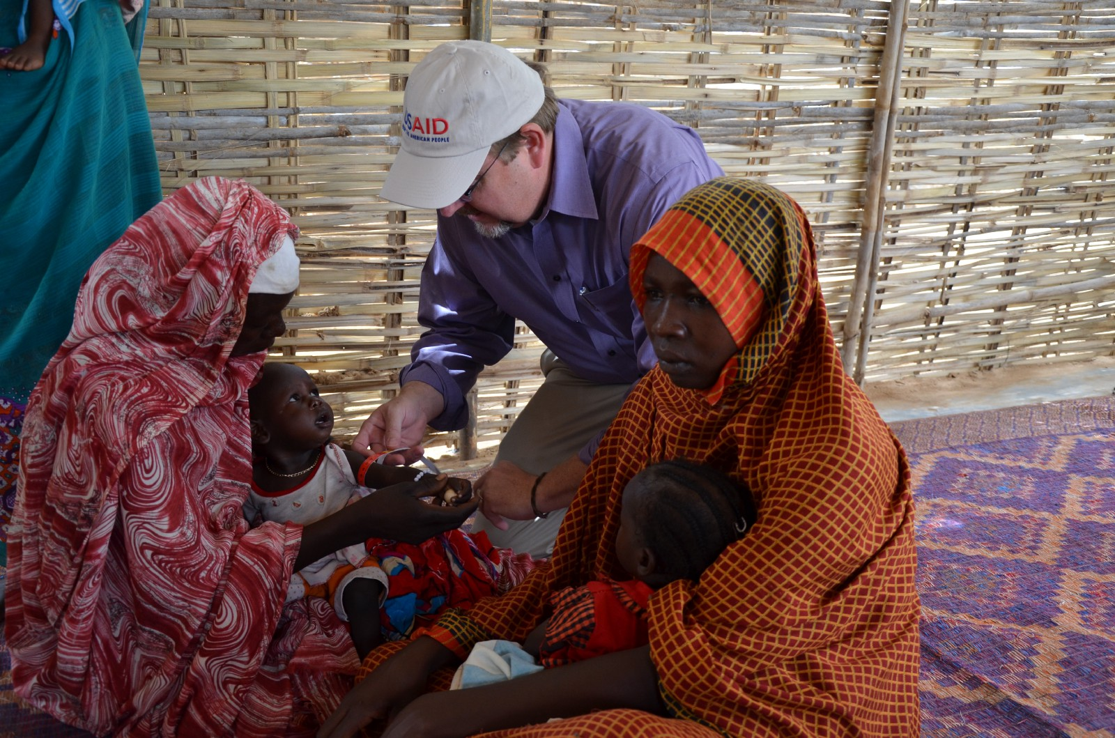 USAID worker kneels while speaking to a mother in traditional dress, holding her small child.
