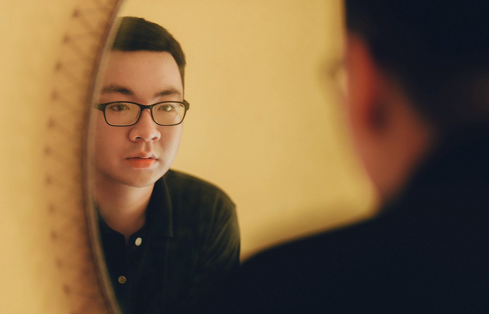 man with glasses looking on the mirror