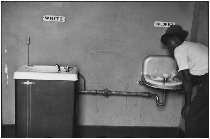 A Photo Of Segregated Fountains With Black Person Drinking At Smaller Dirtier Fountain Labeled Colored