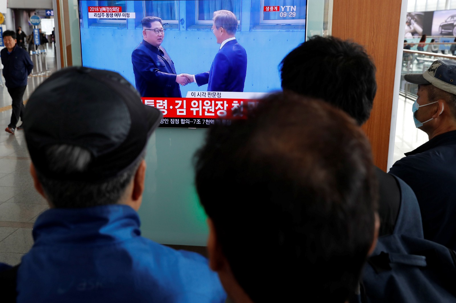 People watch a TV showing a live broadcast of the inter-Korean summit as  South Korean President Moon Jae-in shakes hands with North Korean leader  Kim ...