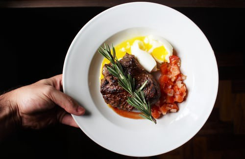 Whether a keto diet breakfast or dinner, you can't go wrong with eggs, steak, and some diced tomato