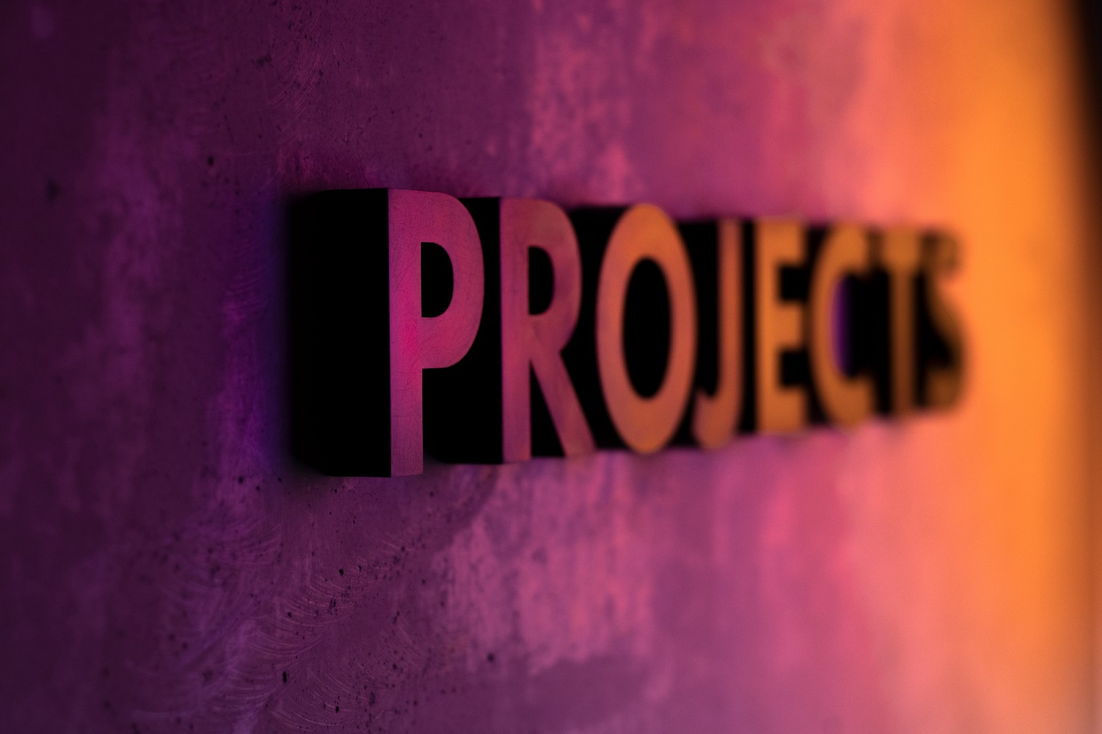 "Letters spelling ""PROJECTS"" attached on the wall with some light reflecting from the back"