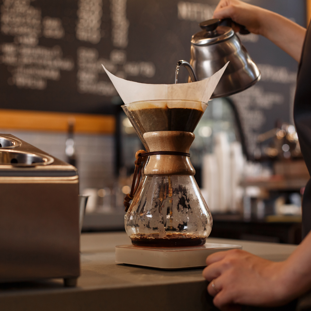 A barista pour hot water into a Chemex coffee brewer to make fresh, great-tasting coffee.