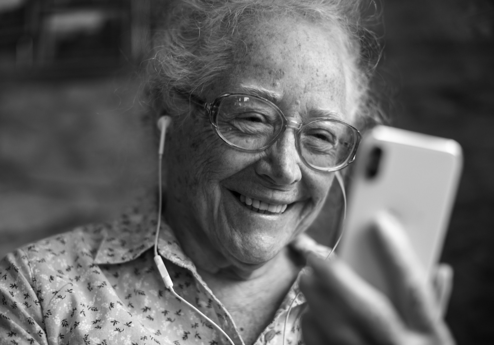An older person wearing ear-pod headphones smiles while looking at their smartphone. Photo credit: Rawpixel viaUnsplash