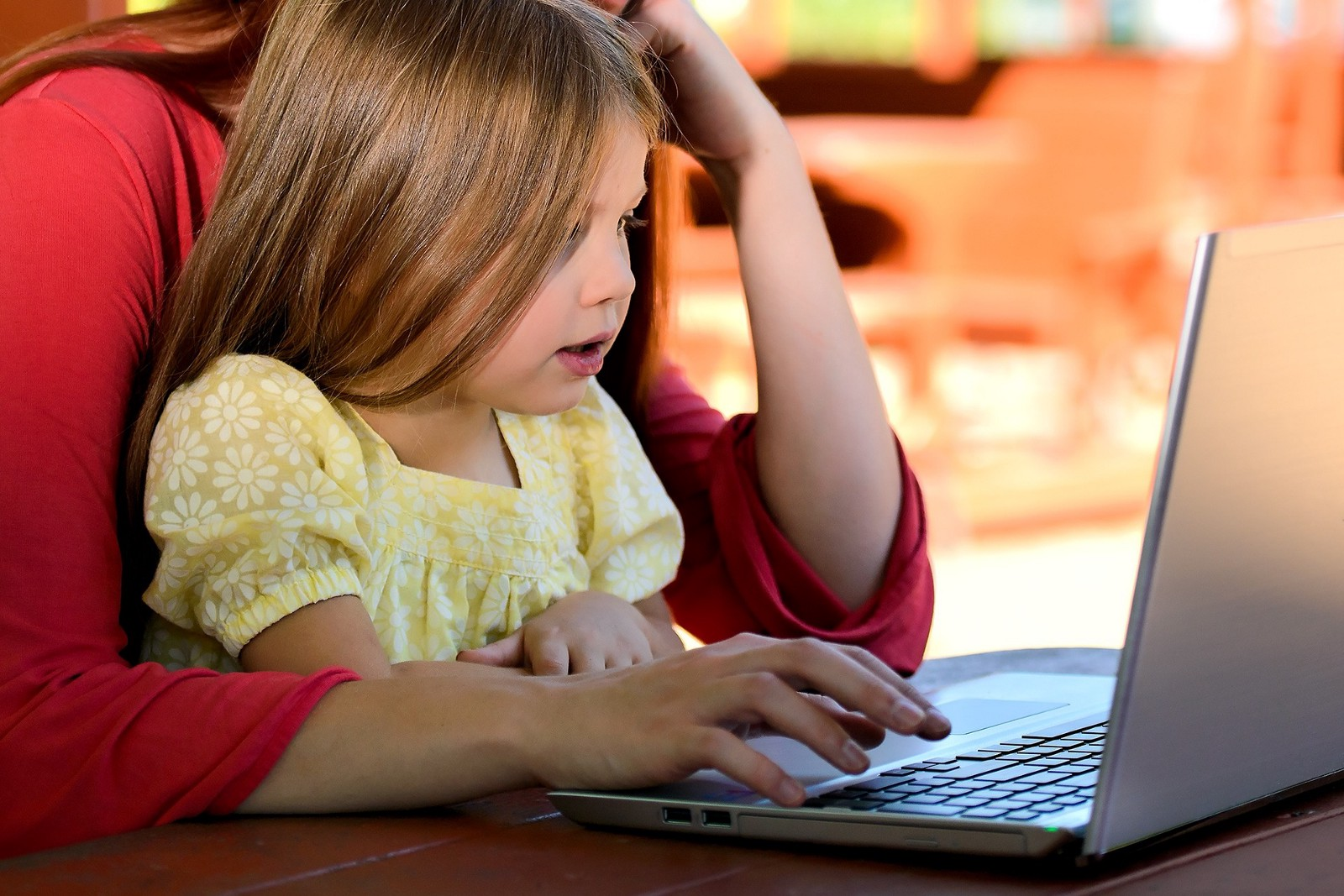 Parent teaching child with computer