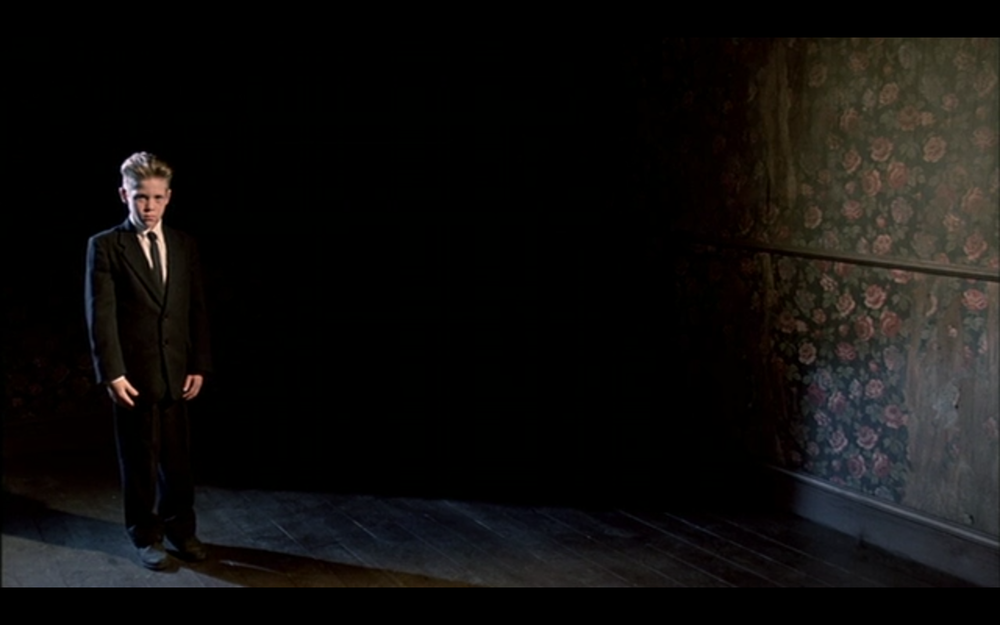 The Magician standing against darkness with the flowered wallpaper in Fire Walk With Me, 1992