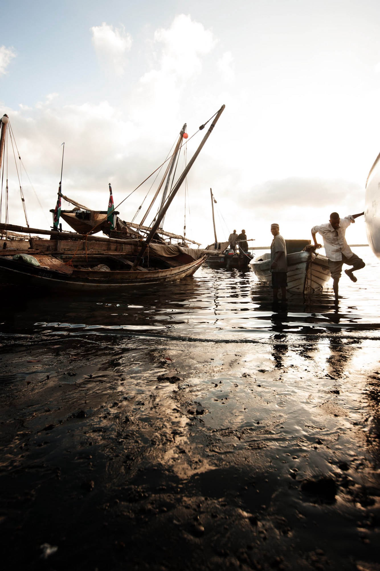 During low tide, fishing dhows keel over in the mud of the Lamu estuary. | © James Fisher 2017 All Rights Reserved.