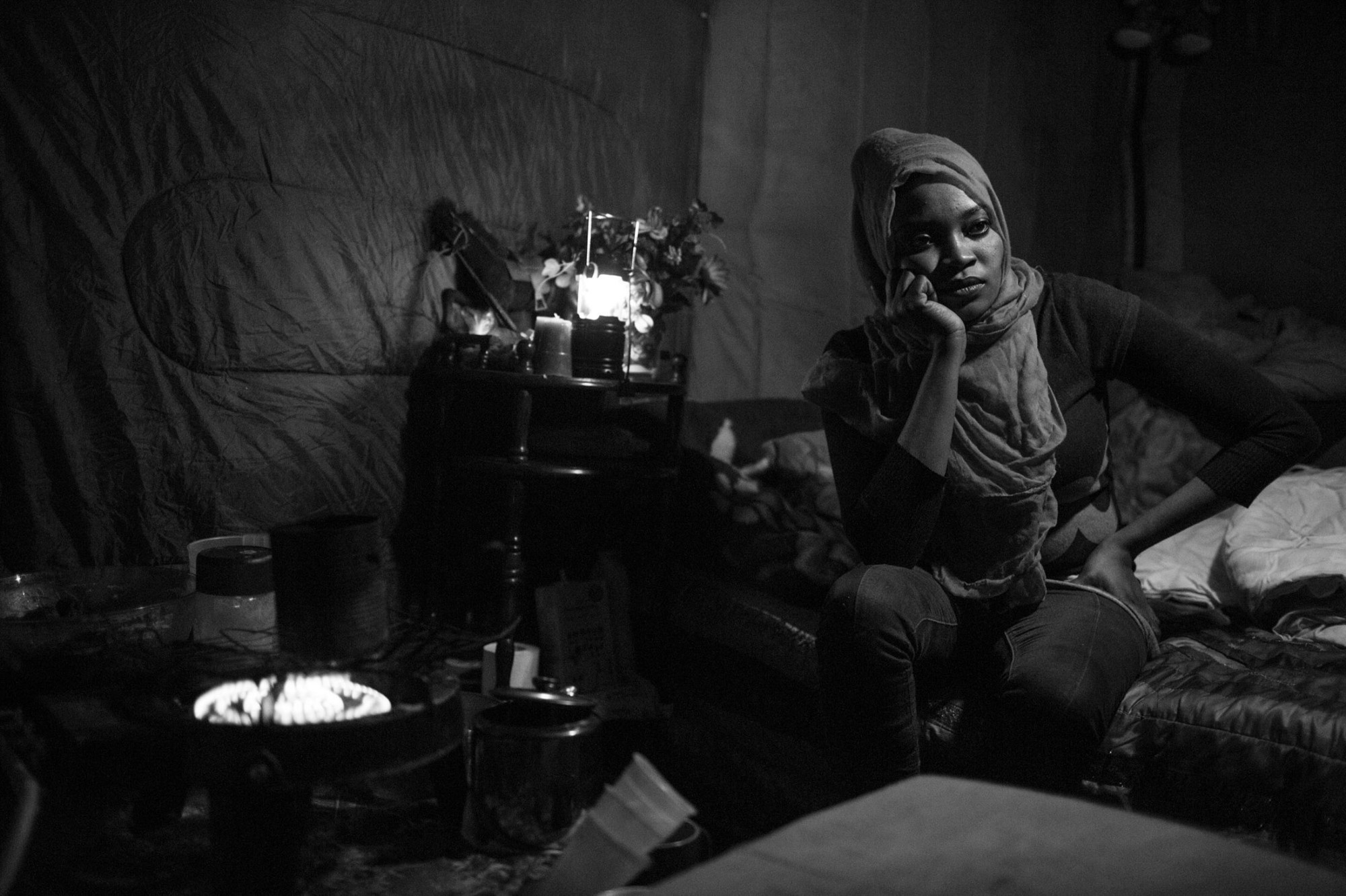 Luna in a reflective mood between cooking meals on a portable propane gas ring and caring for her daughter Euro in a shack insulated by donated sleeping bags, which was built by her husband Hosni. She is one of the many women in the Jungle seeking refuge.