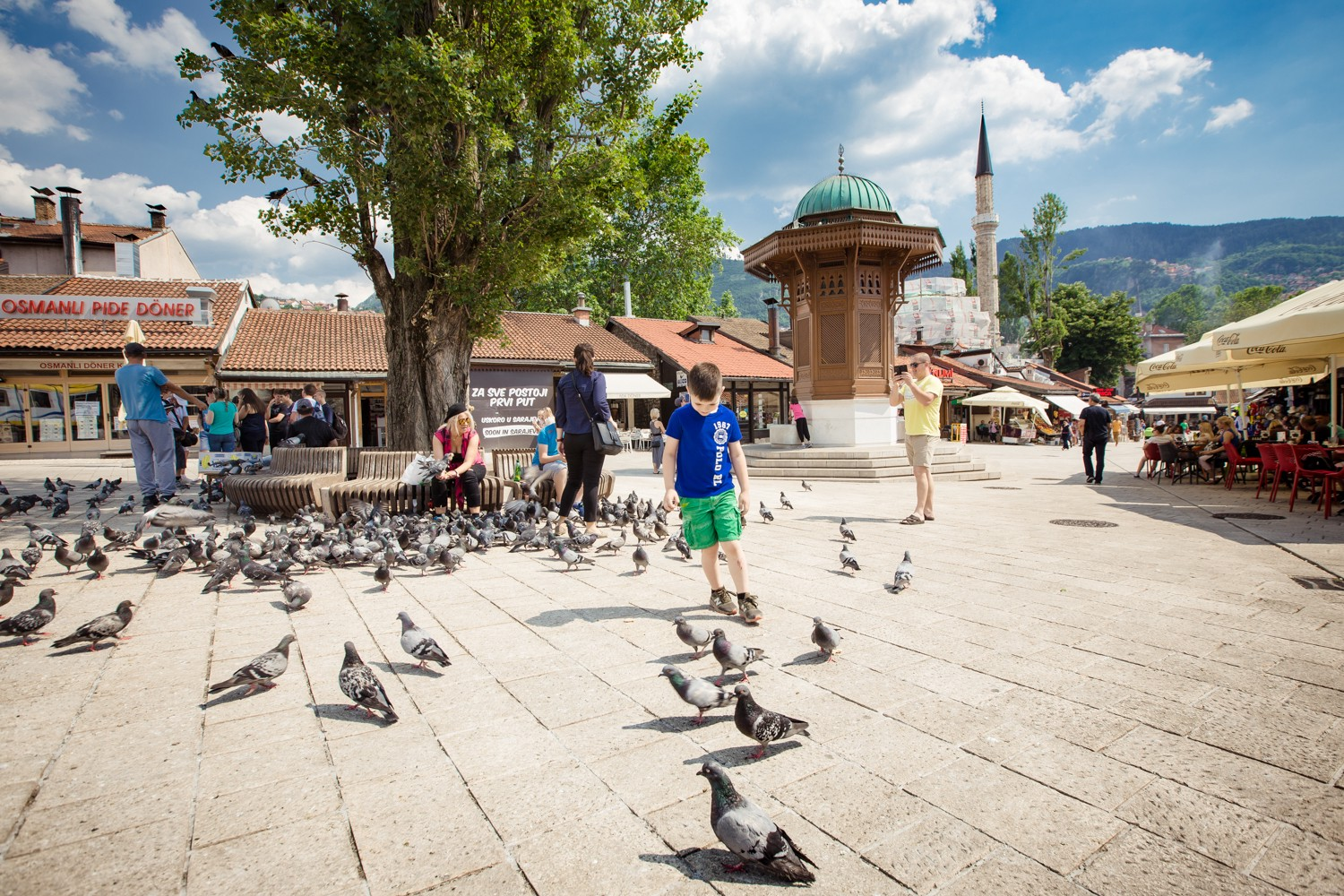 Boy and pigeons against the backdrop of Sebilj, Baščaršija, Sarajevo