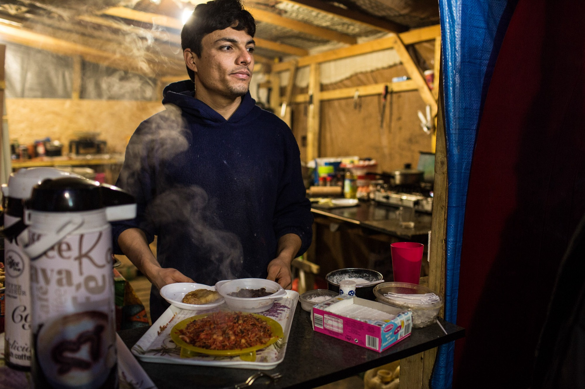 Ali cooks for both Jungle residents and volunteers in his restaurant, which he started with two partners after they failed to reach England.