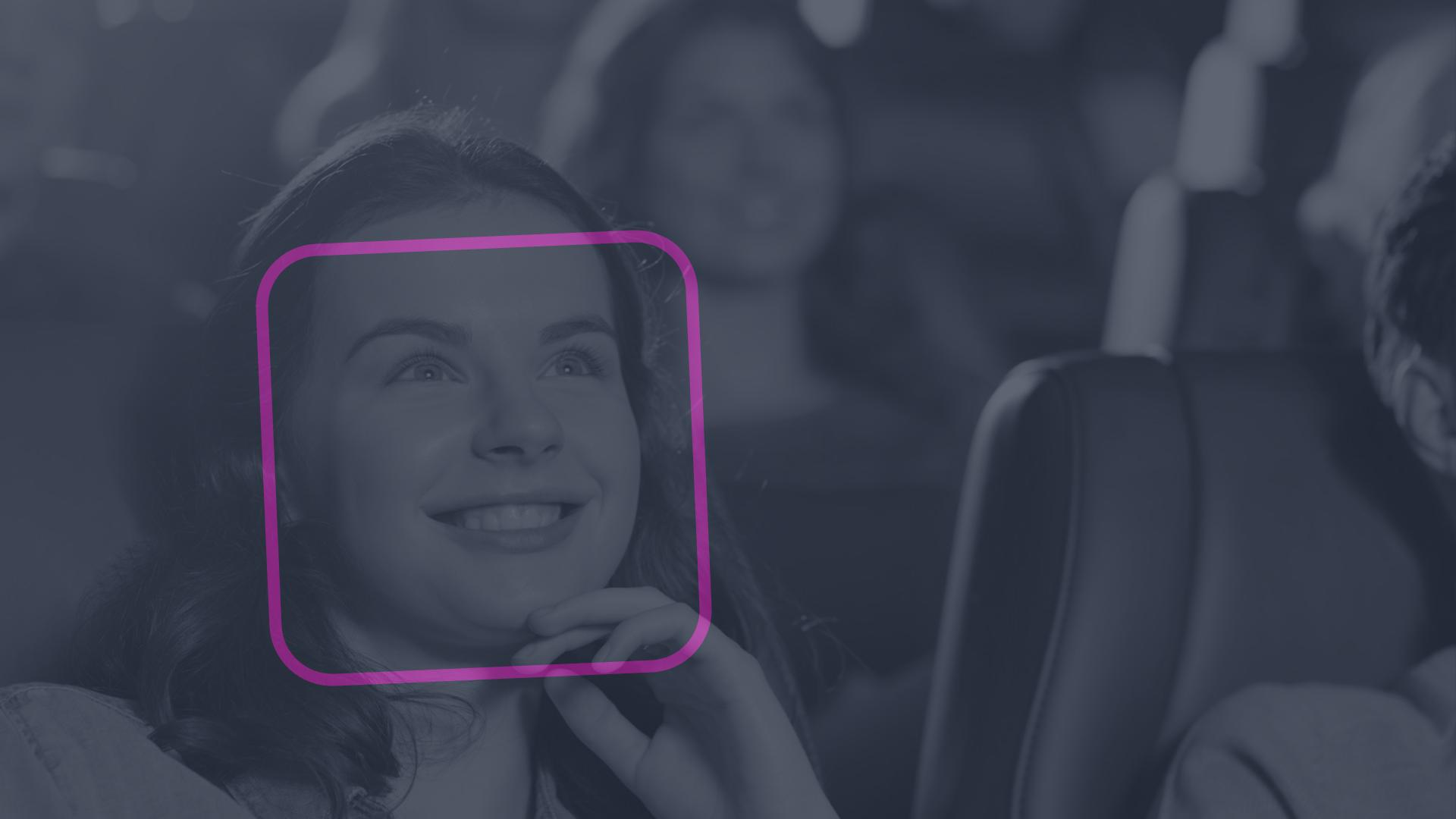 Women watching a movie, with a pink bounding box over her face