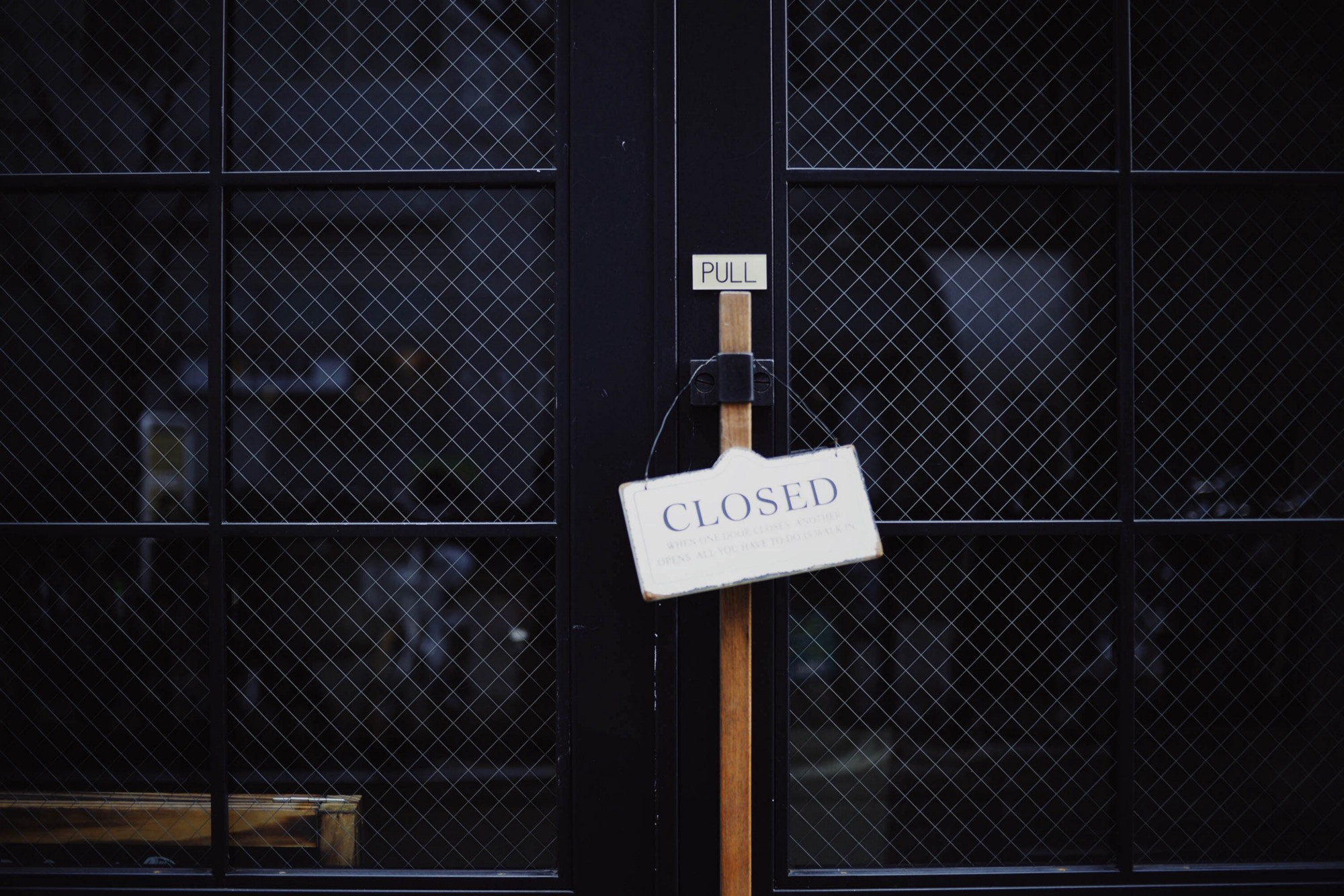 """A sign saying """"closed"""" on a dark storefront."""