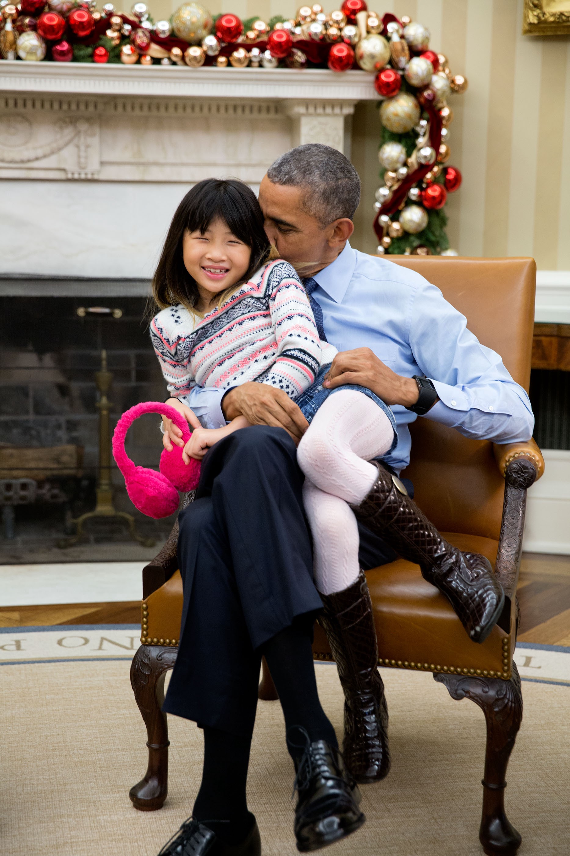 "Dec. 4, 2015 ""The President snuggles with his niece Savita Ng after his sister, Maya Soetoro-Ng, and her family dropped by the Oval Office."" (Official White House Photo by Pete Souza)"