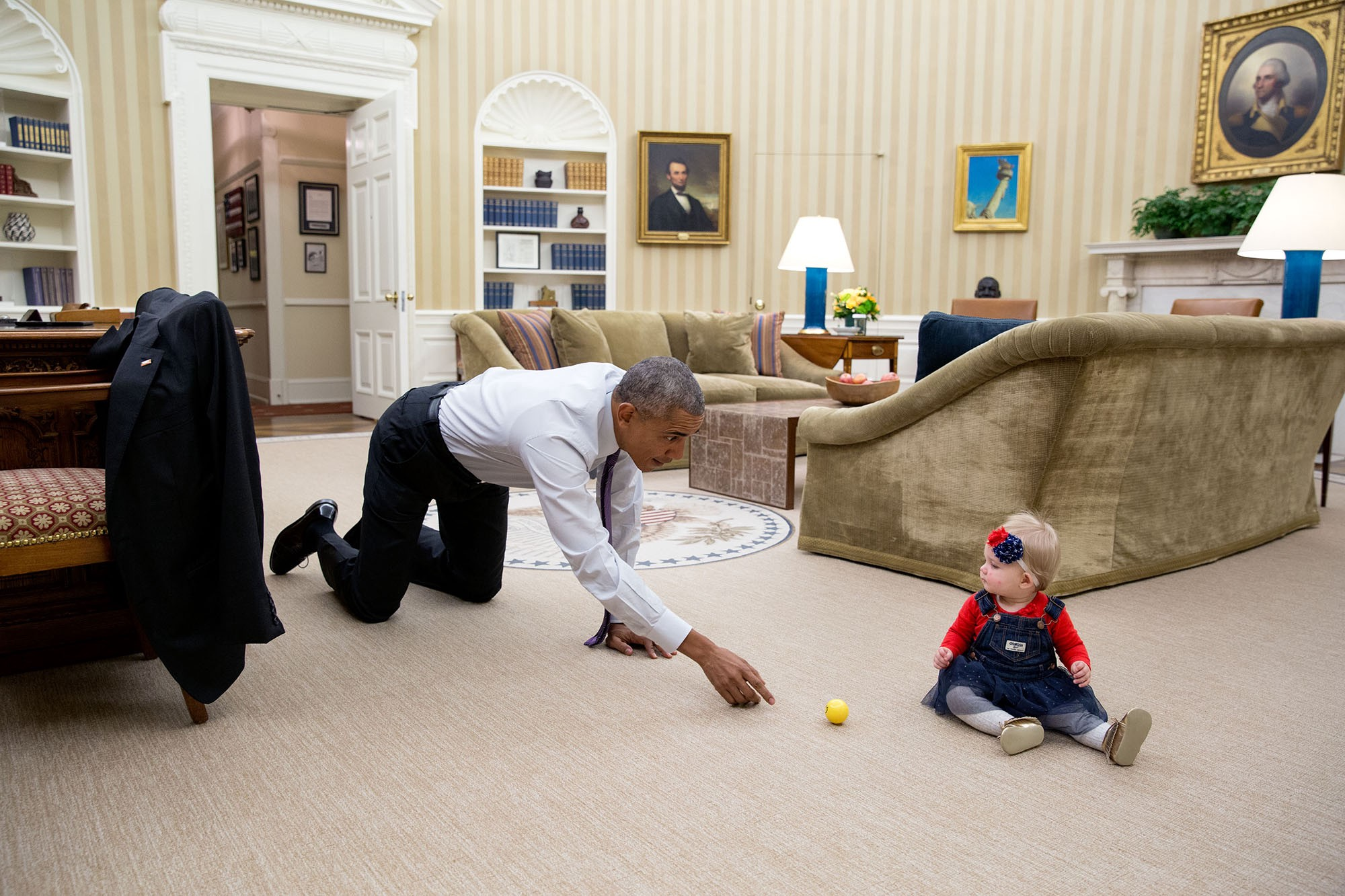 "Nov. 8, 2016 ""The President had just walked in from the dining room and sitting on the floor in the Oval Office was Evelyn 'Evie' Cushman, daughter of Chase Cushman, Director of Scheduling and Advance. He immediately dropped down to his hands and knees and began tossing a ball back and forth with her."" (Official White House Photo by Pete Souza)"