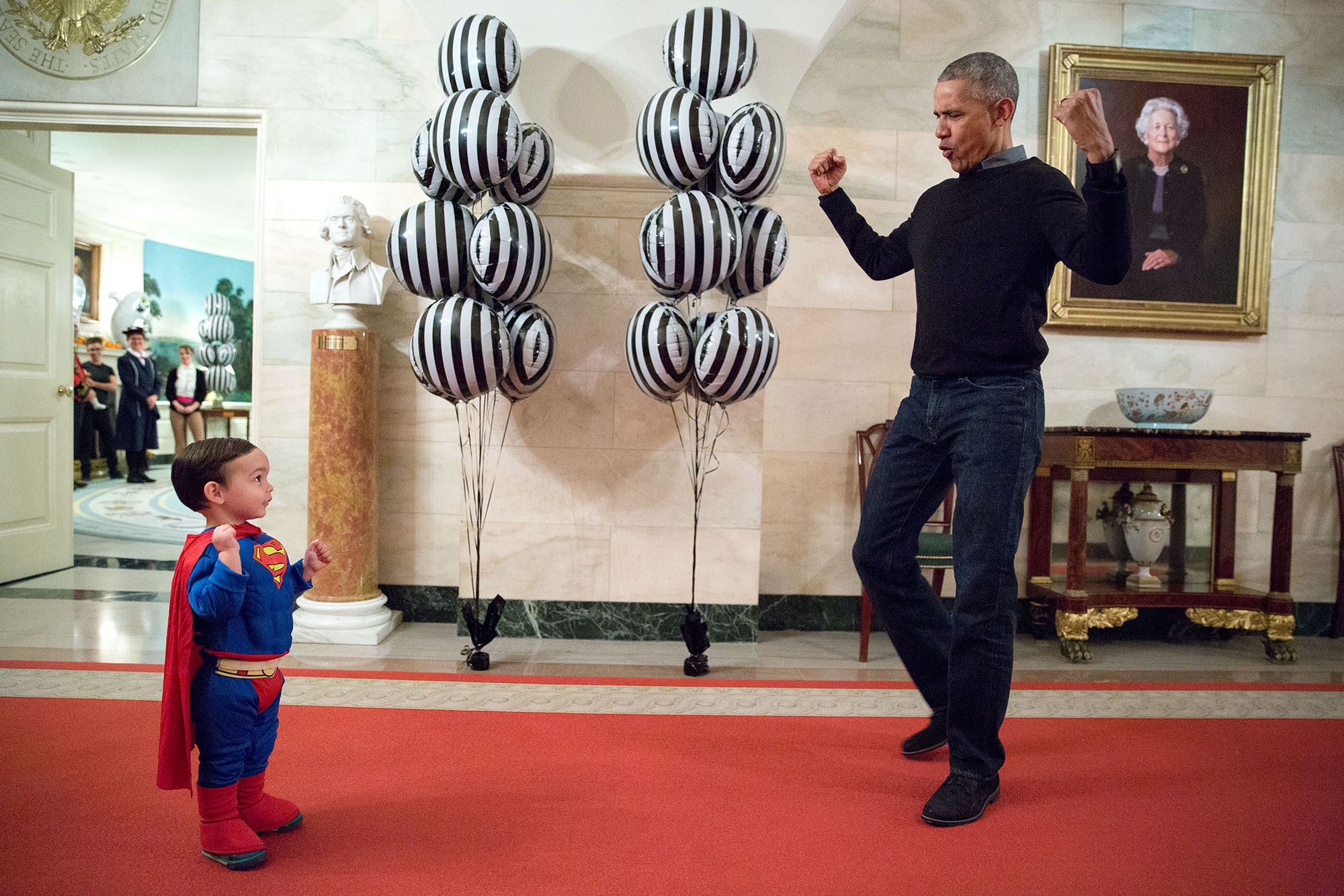 "Oct. 31, 2016 ""The President was about to welcome local children for Halloween trick-or-treating when he ran into Superman Walker Earnest, son of Press Secretary Josh Earnest, in the Ground Floor Corridor of the White House. 'Flex those muscles,' he said to Walker."" (Official White House Photo by Pete Souza)"