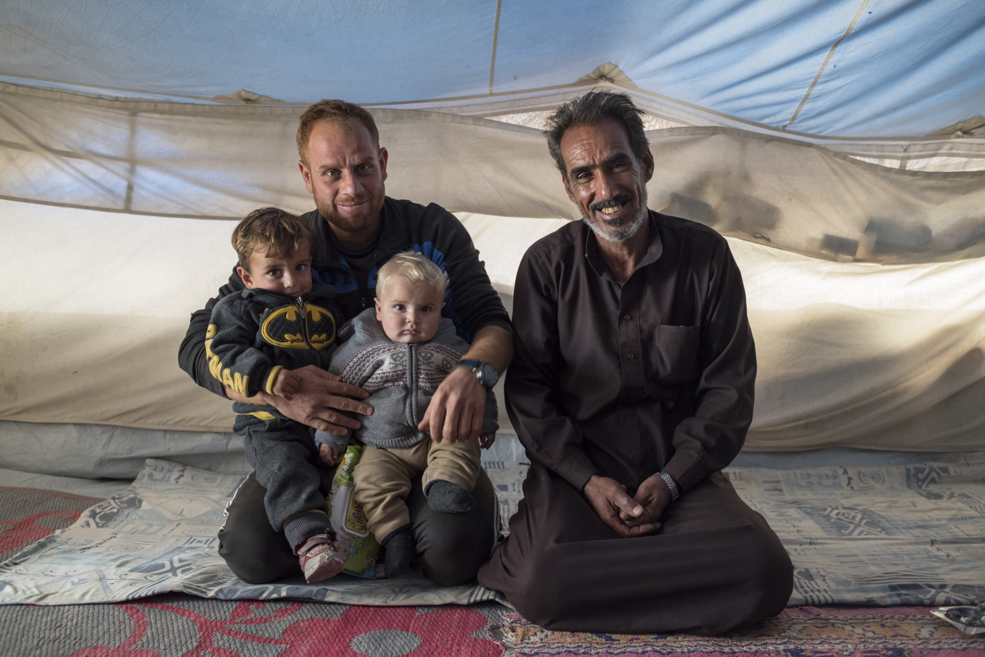 nasser right and his son grandson and a friend in their tent in ain issa camp