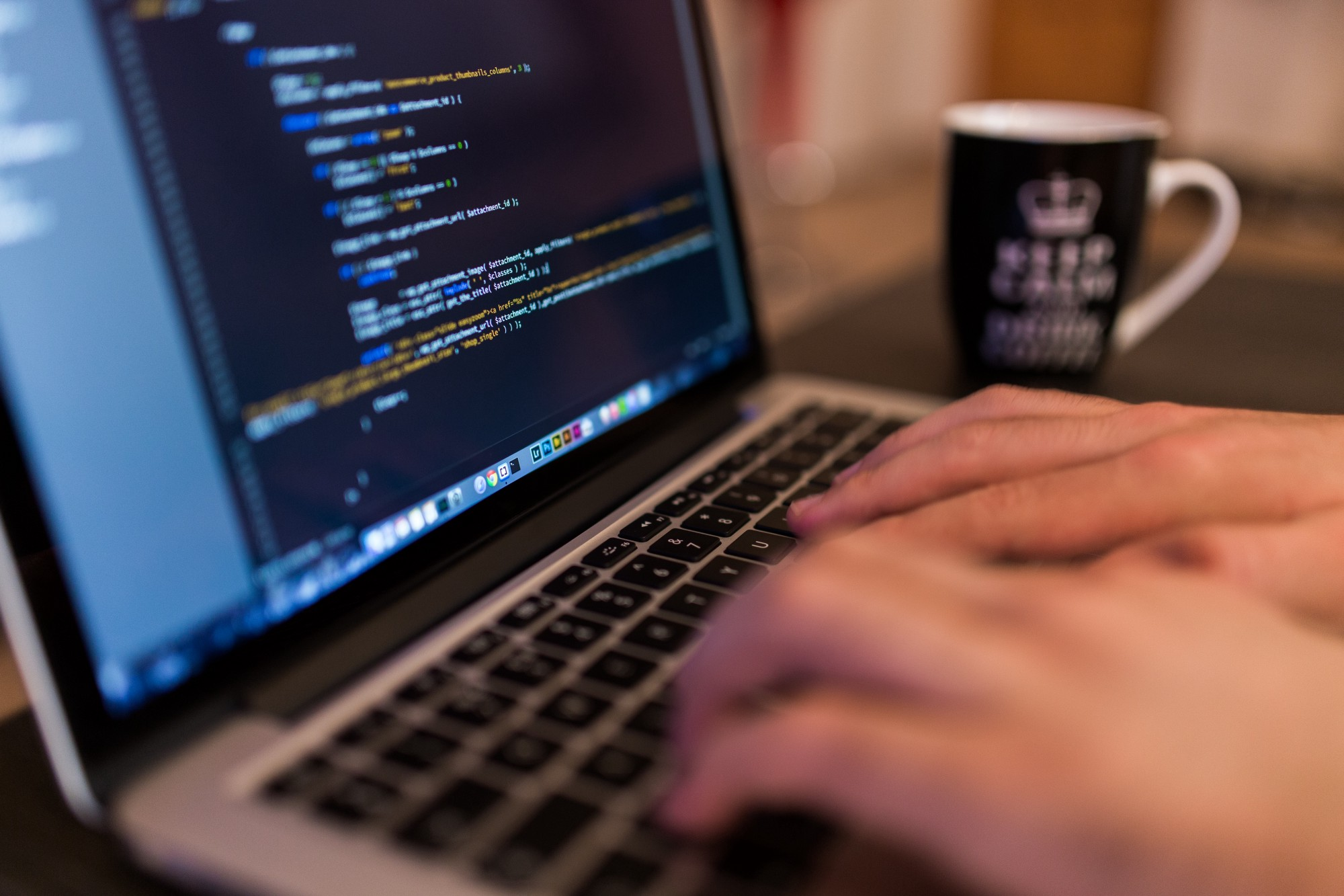 Someone coding (probably Javascript) on a Mac and drinking coffee or tea. Courtesy of Unsplash.