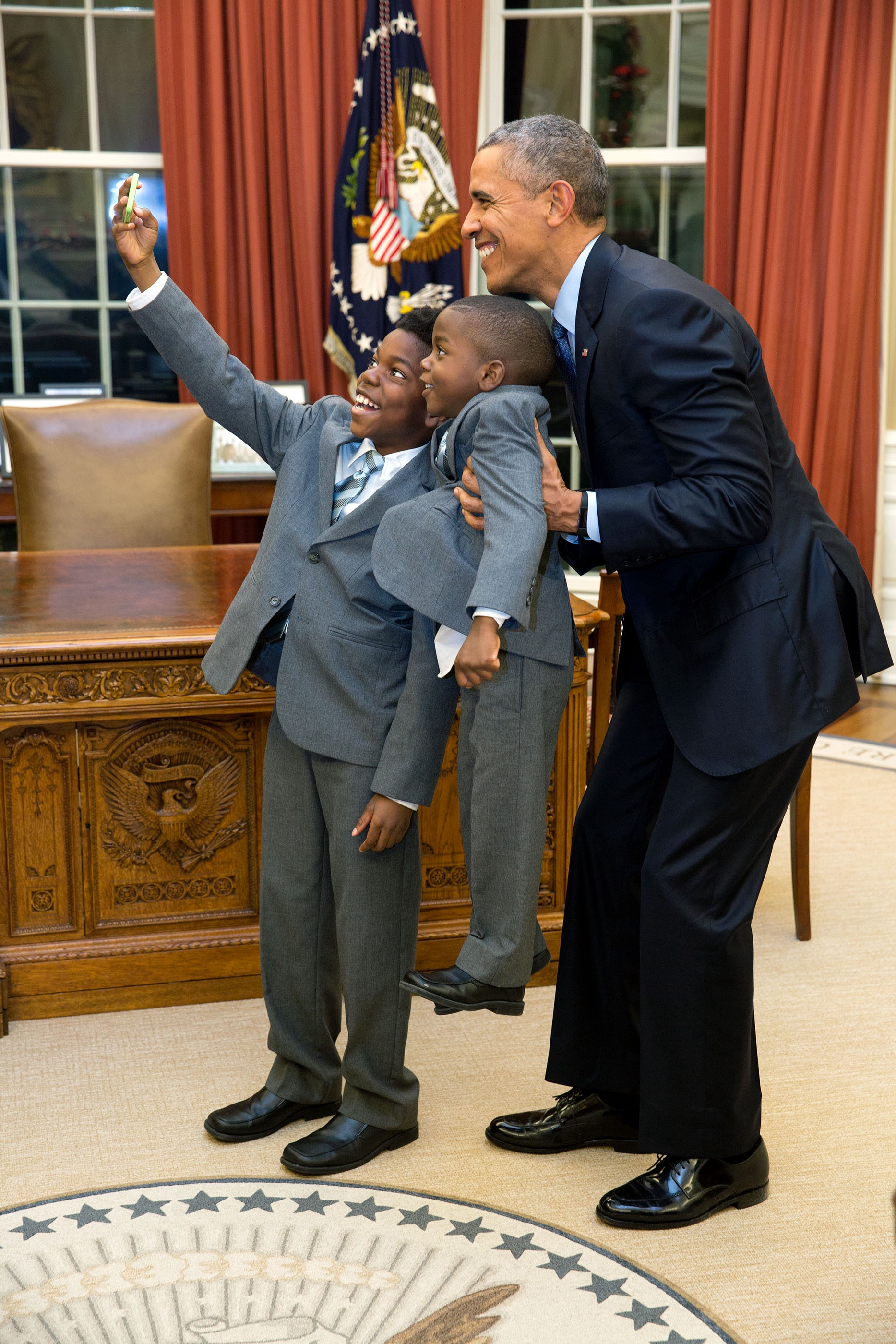 "Dec. 4, 2015 ""The President acquiesced to a selfie with 11-year-old Jacob Haynes and four-year-old James Haynes after taking a family photograph with departing White House staffer Heather Foster."" (Official White House Photo by Pete Souza)"