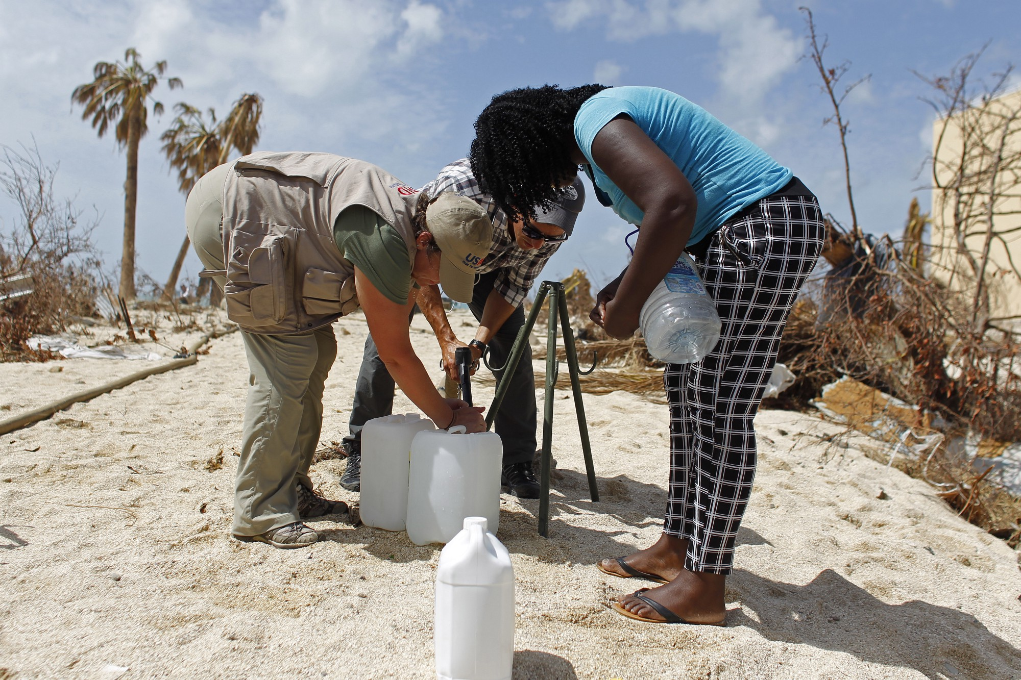 On St. Martin, a member of Joint Task Force-Leeward Islands (center) and DART member Anne Galegor (left) help a local resident to fill a water jug with filtered sea water made potable through a reverse osmosis process. The U.S. military produced a total of 83,020 gallons of potable water for St. Martin during its mission. Photo credit: Ricardo ARDUENGO/AFP