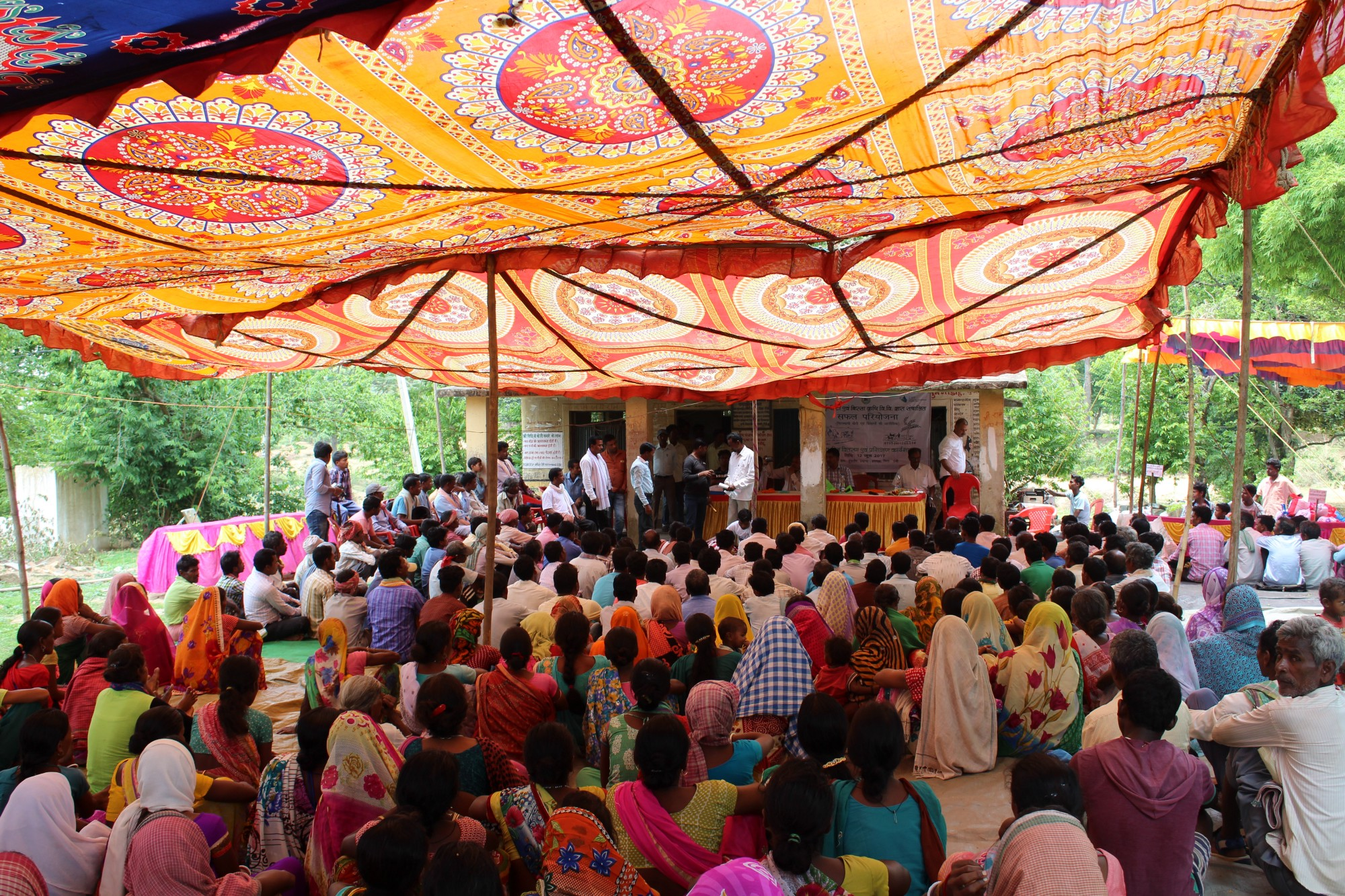Farmers gathered under a tent to collect their bags of high-yielding rice seeds. / Neha Khator, USAID