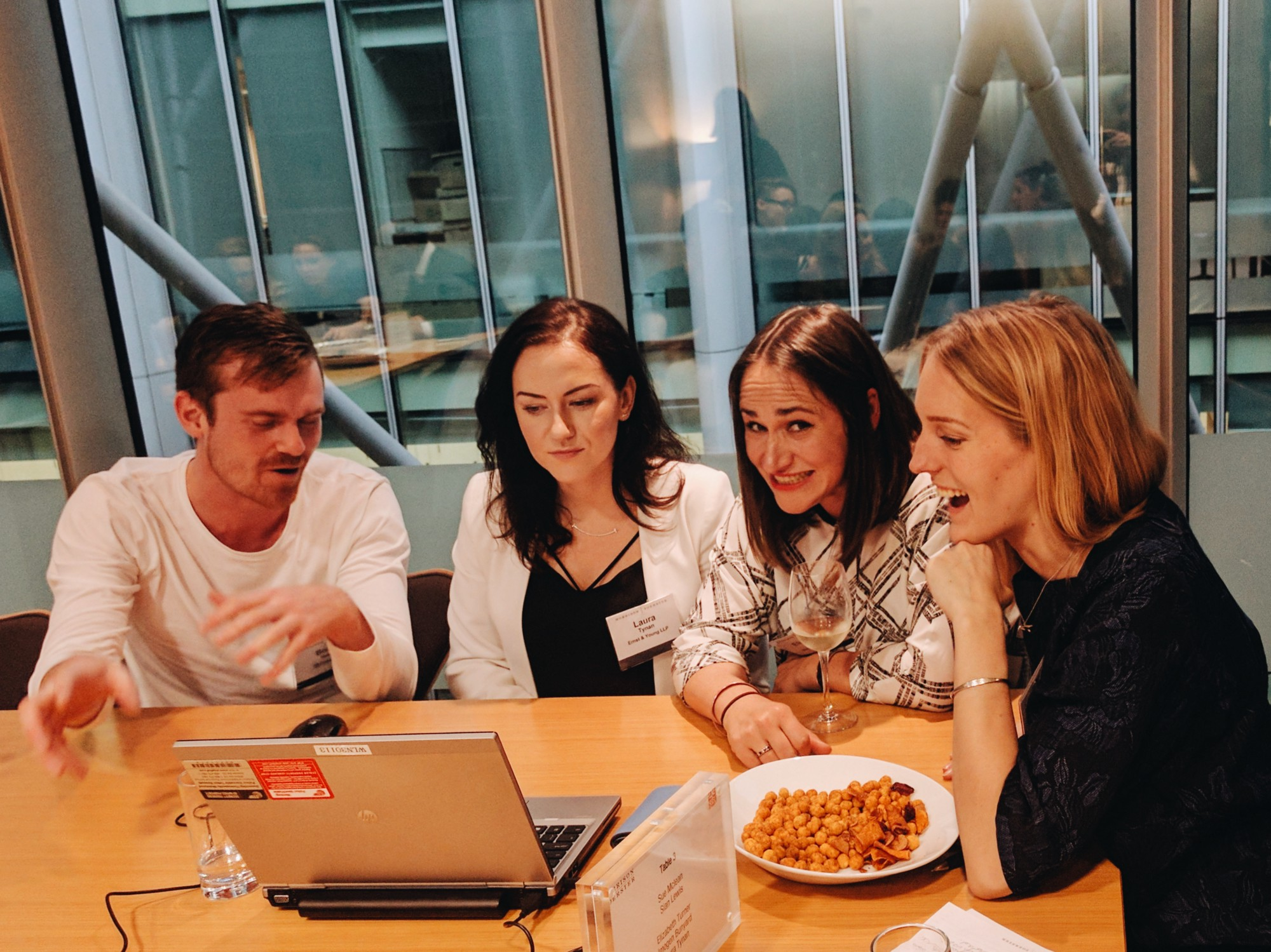 Developer and teacher, Bobby, with three women at a laptop with drinks and peanuts. One woman looks cheekily at the camera.