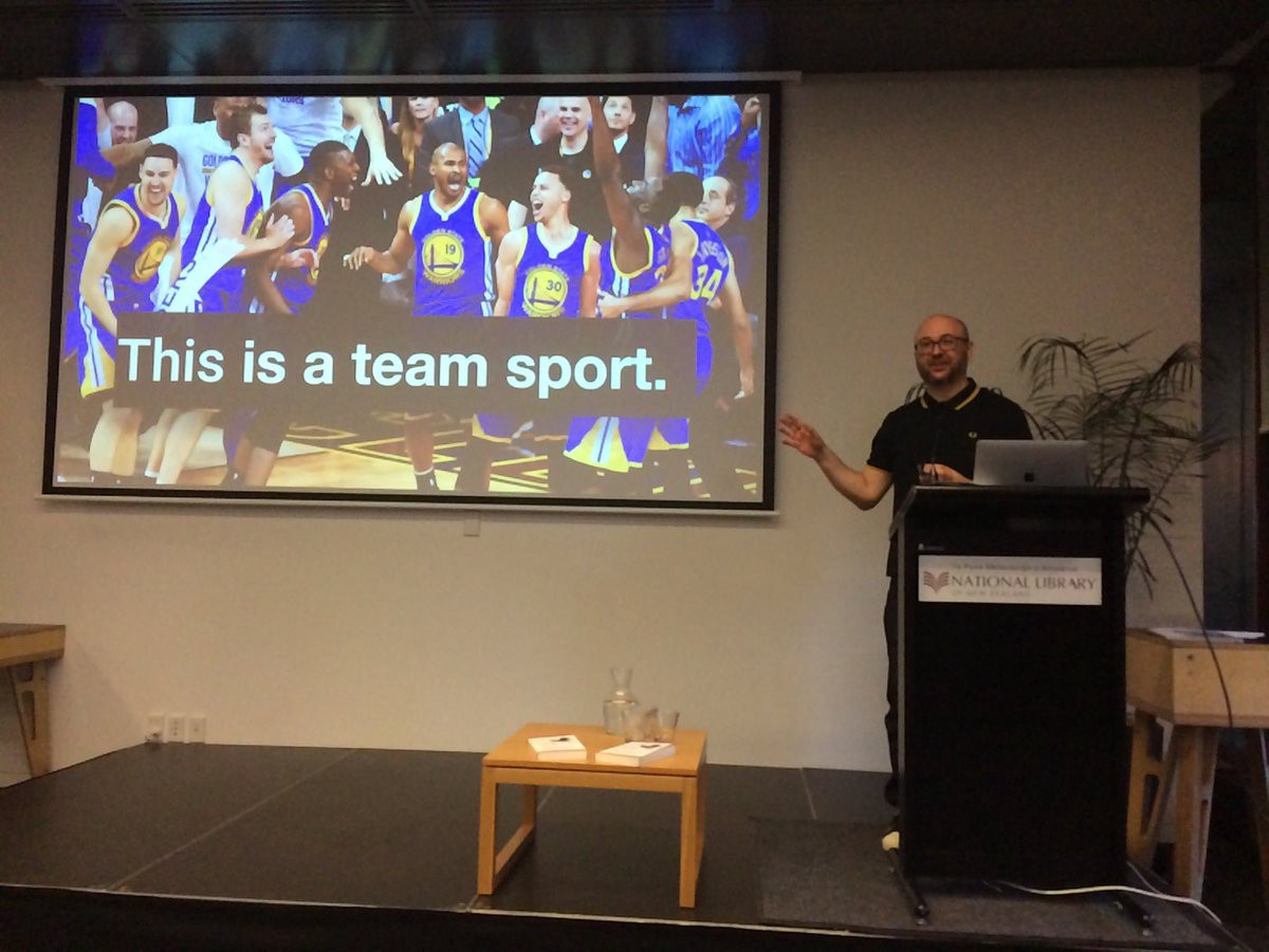 a guest presenter mid-speech standing in front of a projector screen with a slide that reads 'this is a team sport''
