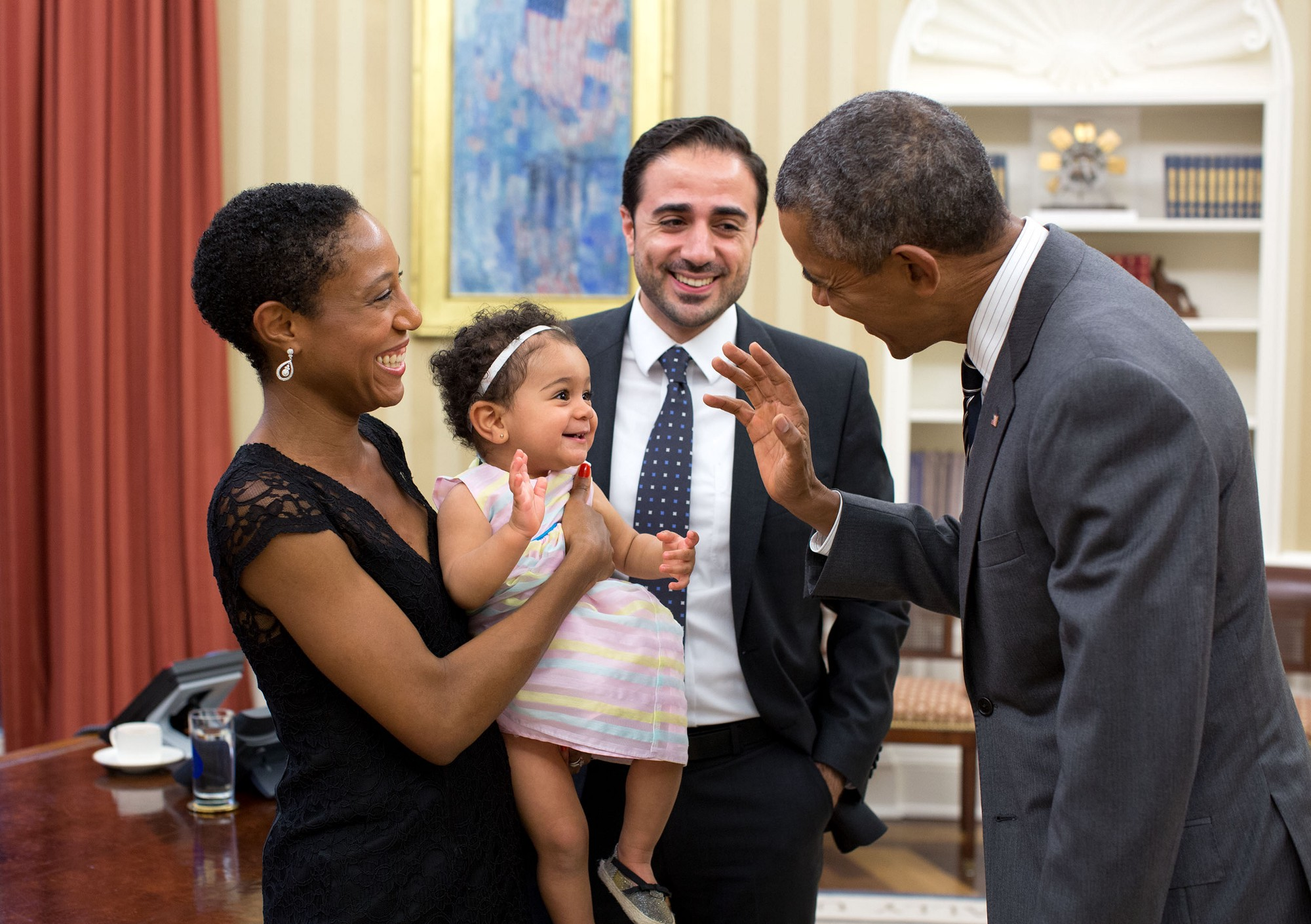 "Sept. 21, 2015 ""The President exchanges a wave with Alya Dorelien Bitar, one-year-old daughter of Maher Bitar, the outgoing National Security Council Director for Israeli and Palestinian Affairs, and his wife, Astrid Dorelien, during a family photo in the Oval Office."" (Official White House Photo by Pete Souza)"