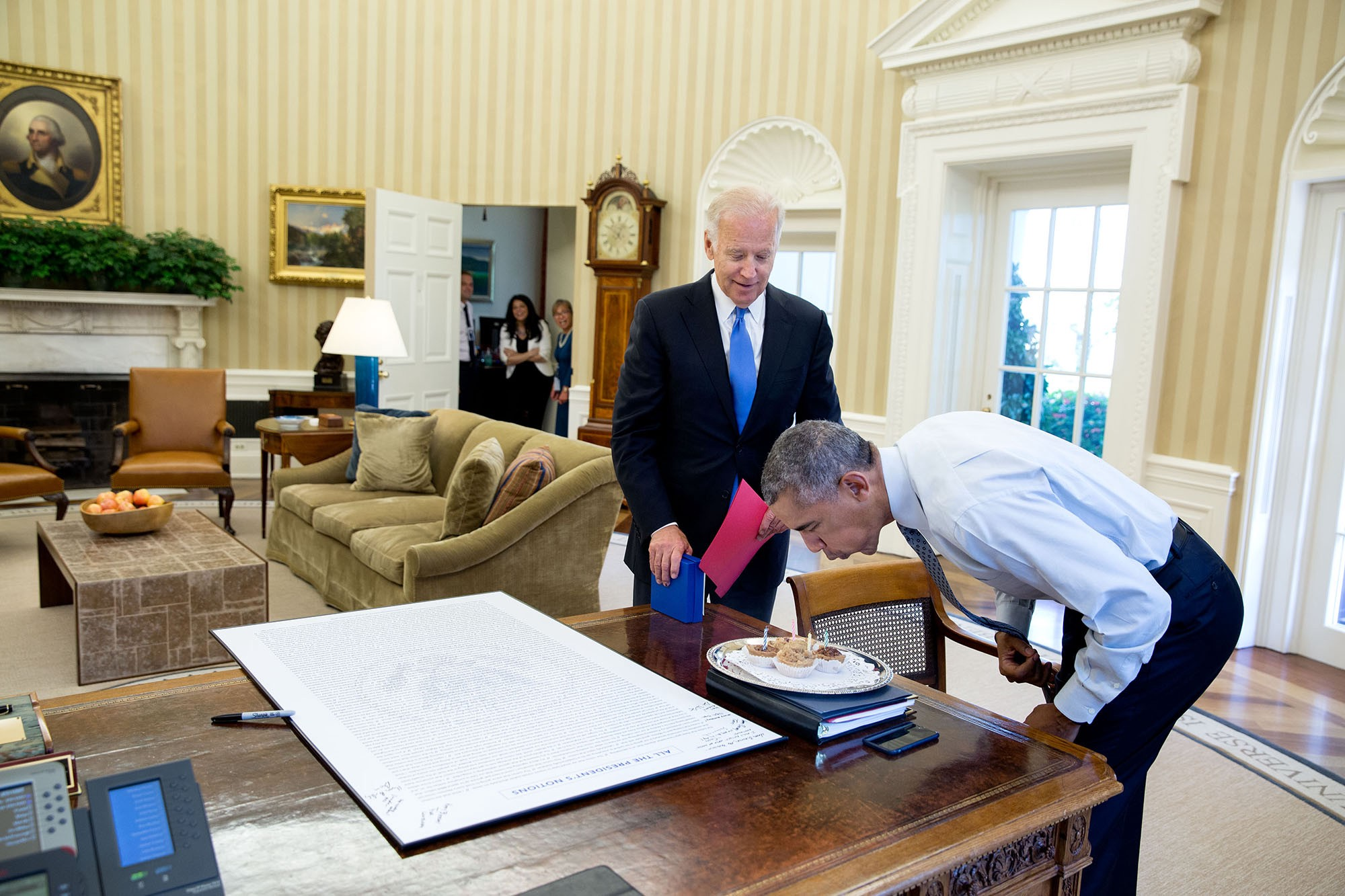 "Aug. 4, 2016 ""With some staff watching in the background, President Obama blows out candles after the Vice President surprised him with some birthday cupcakes."" (Official White House Photo by Pete Souza)"
