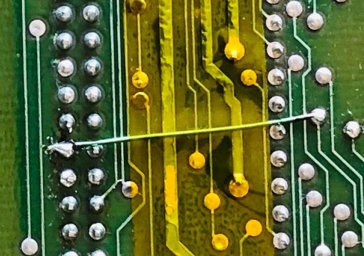 A bodge wire on the underside of the PCB, protected with kapton tape