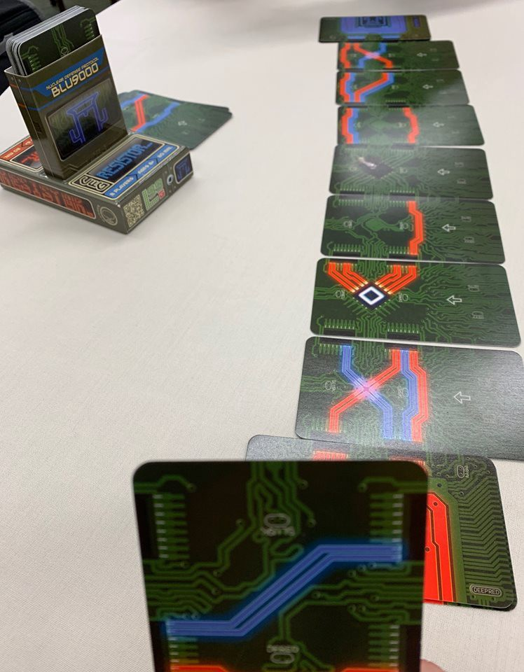 This 2-player game called RESISTOR_ allows 2-players to try and connect wires and paths to one another. It is a unique game because i'm playing with the front of the cards I have but also the backs of the cards of the other player. It uses memory in ways I haven't seen before.