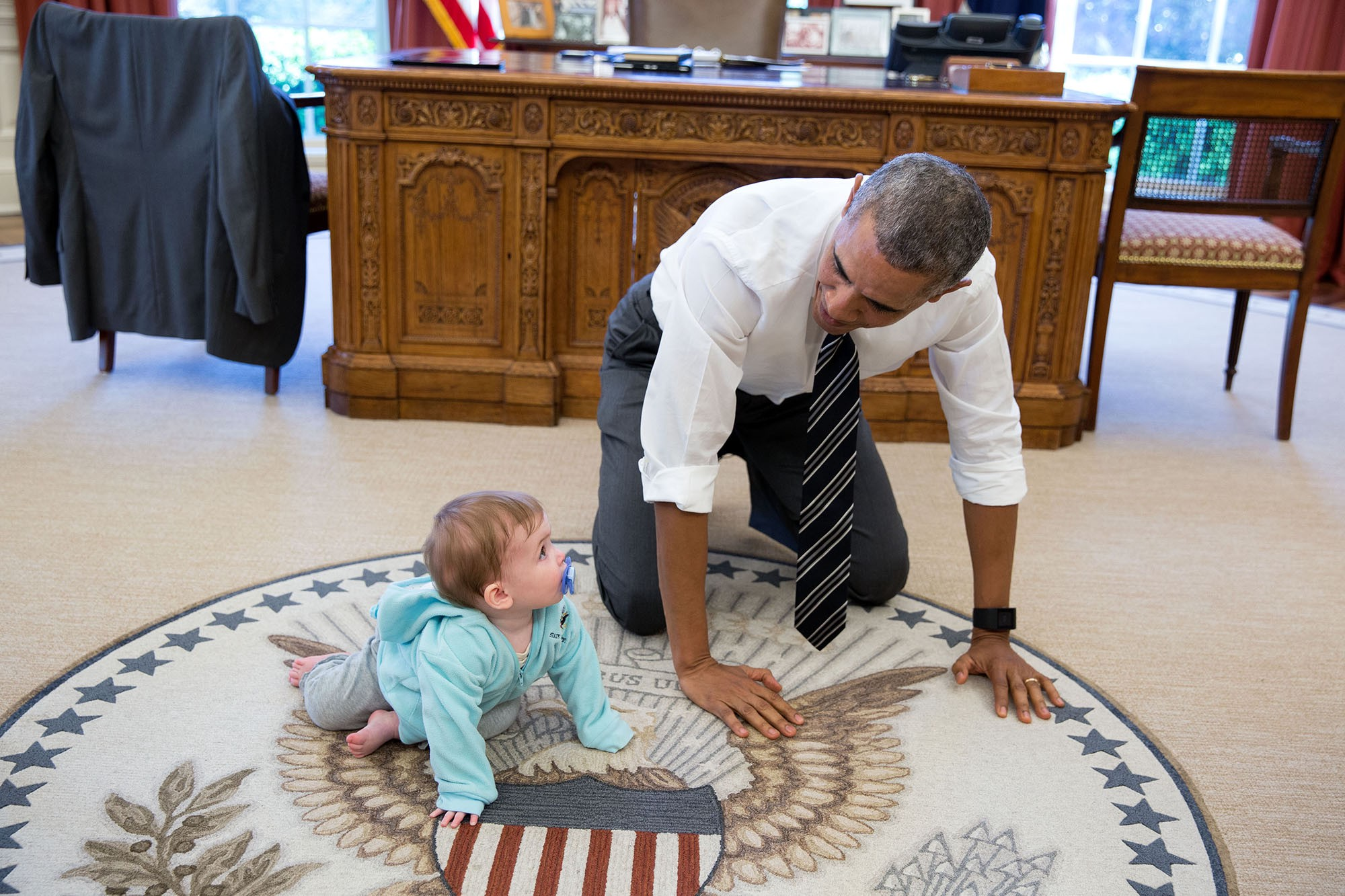 "April 14, 2016 ""The President is always asking staff to bring their babies and young kids by for a visit. Here, during a break between meetings one afternoon, the President crawled around in the Oval Office with Communications Director Jen Psaki's daughter Vivi."" (Official White House Photo by Pete Souza)"