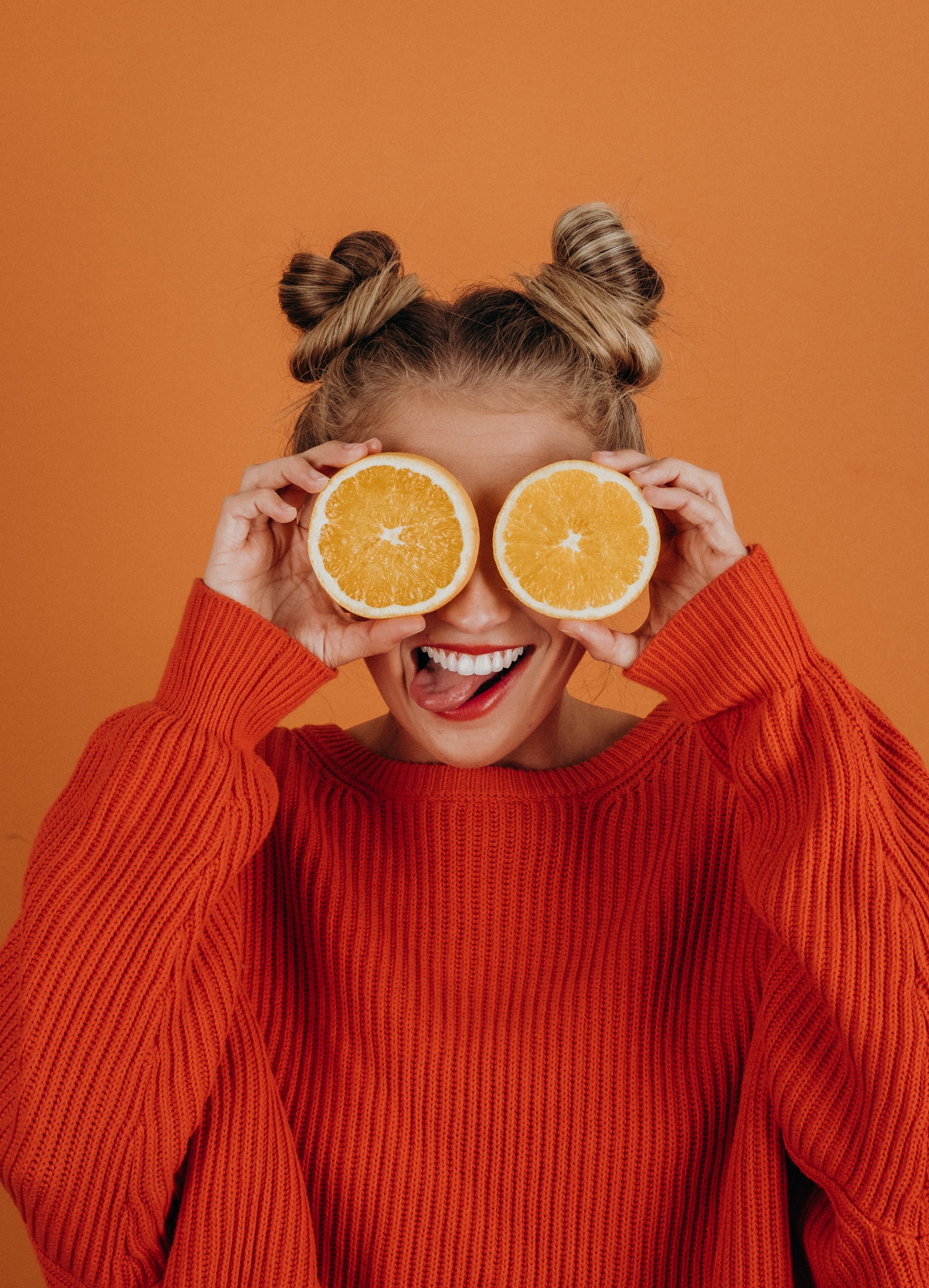 woman holding two oranges against her eyes and grinning