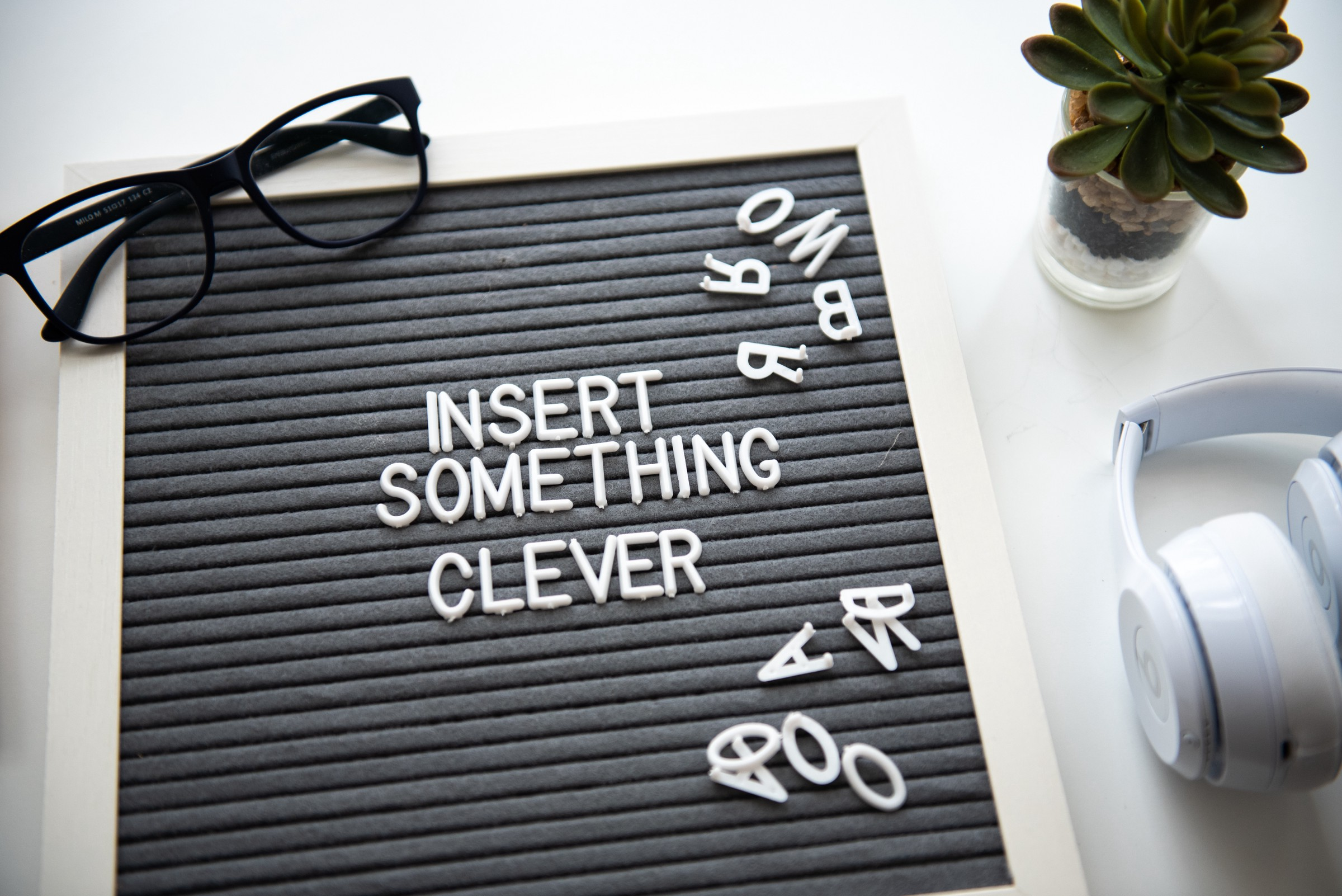 a black notice board with the words 'insert something clever' and a pair of black glasses and a plant