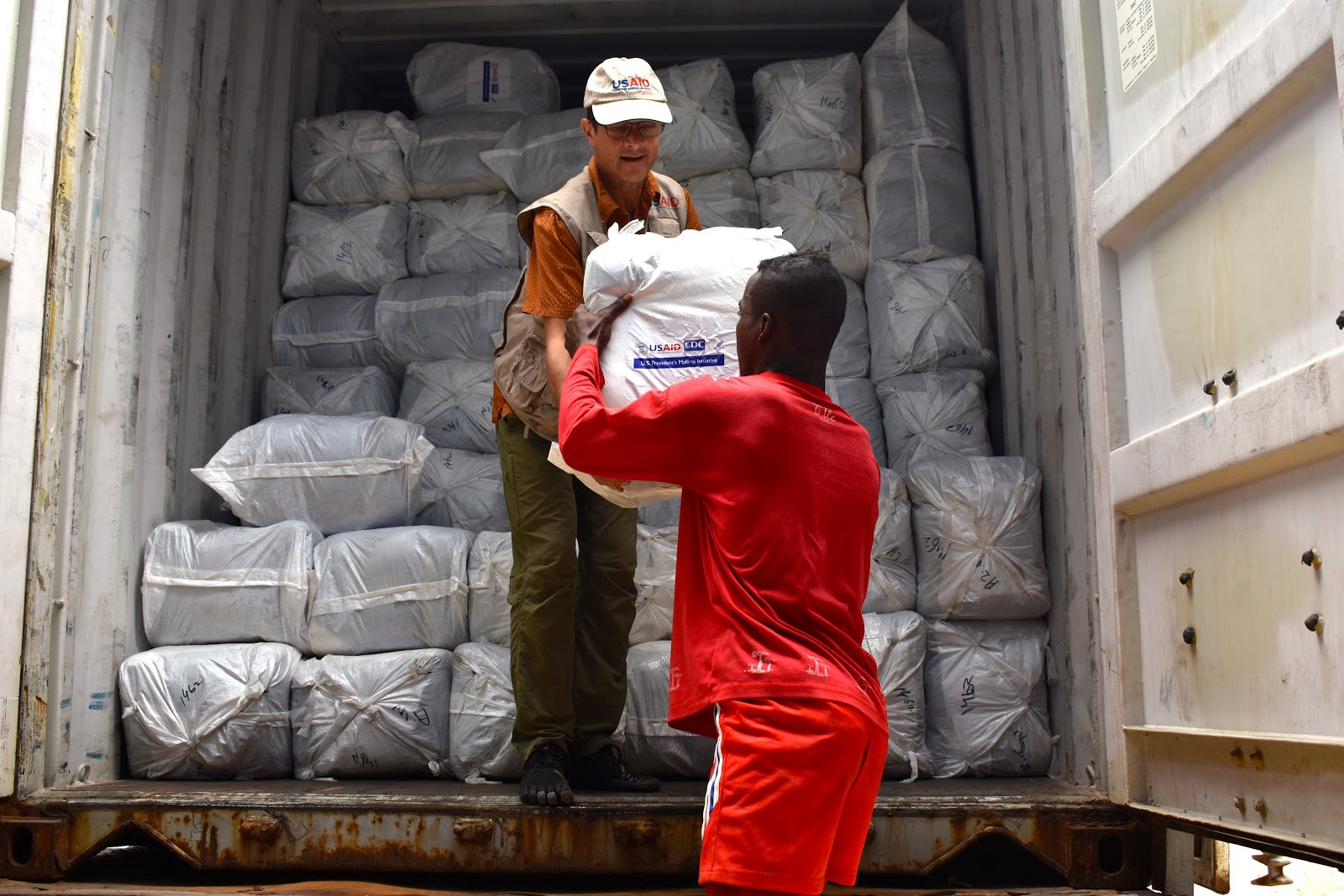 Bed nets are off-loaded from trucks into a warehouse in Antananarivo. / Anne Daugherty, USAID Madagascar
